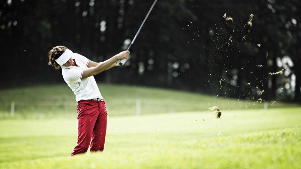 a woman swinging a golf club on a green fairway