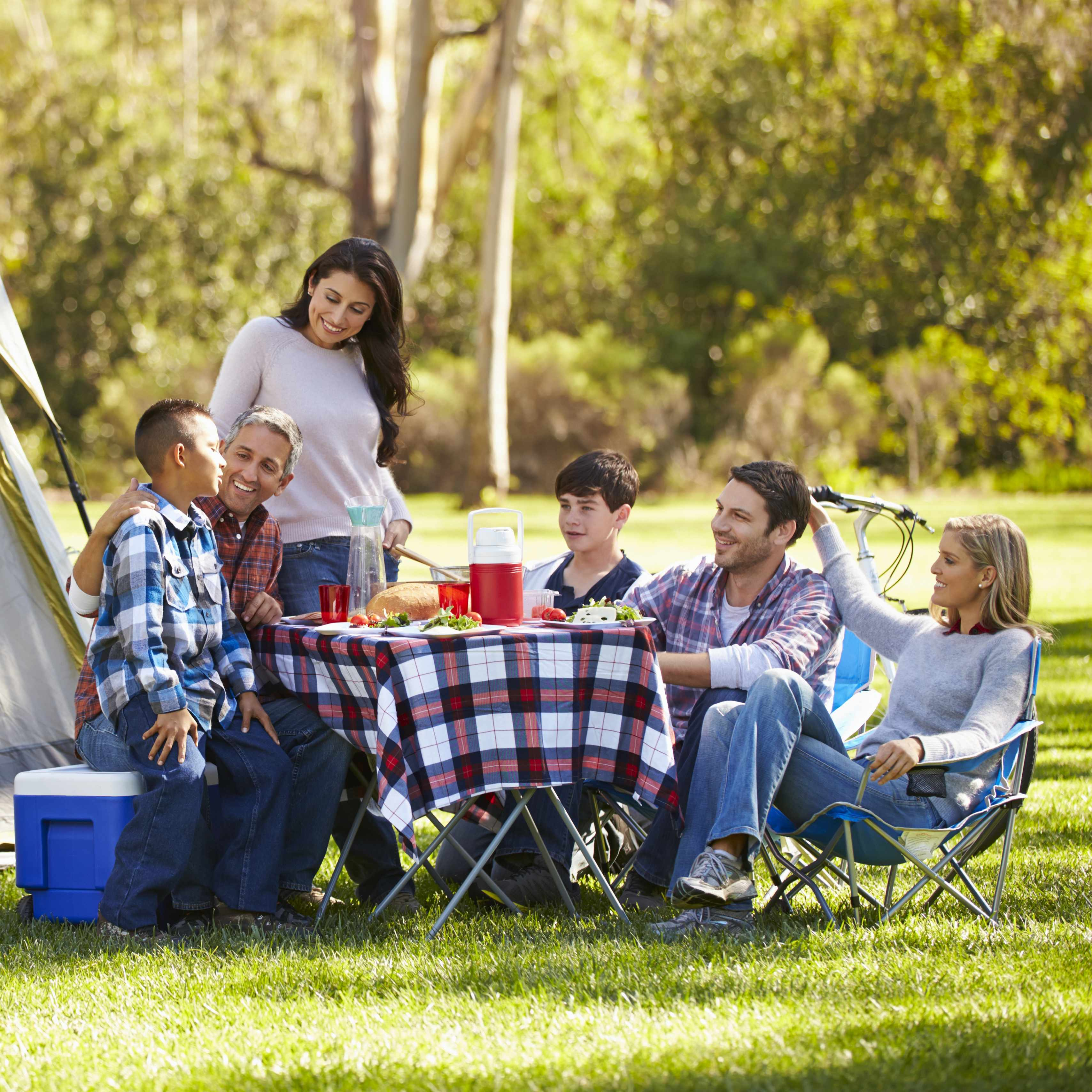 family and friends camping outdoors in a wooded area or park