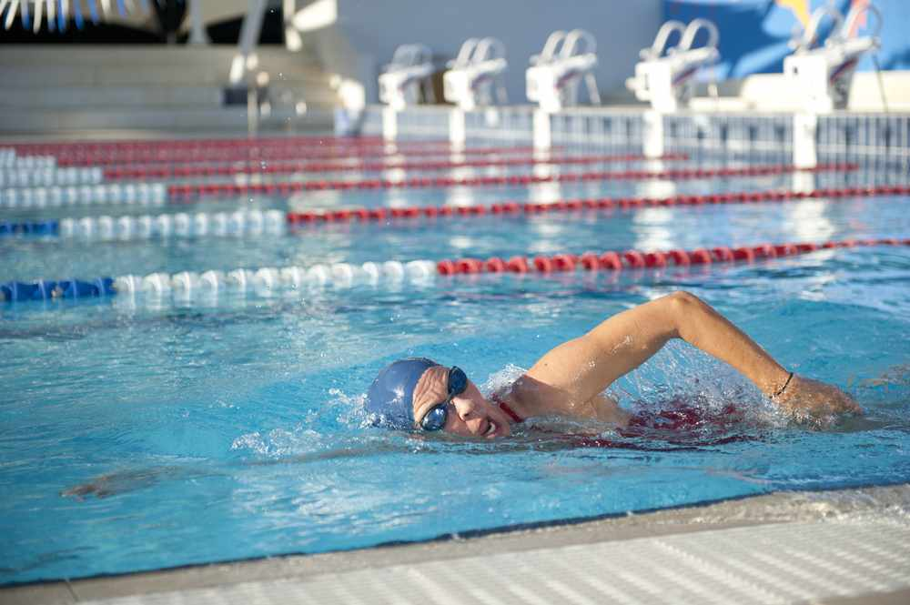 a woman swimming laps in a pool