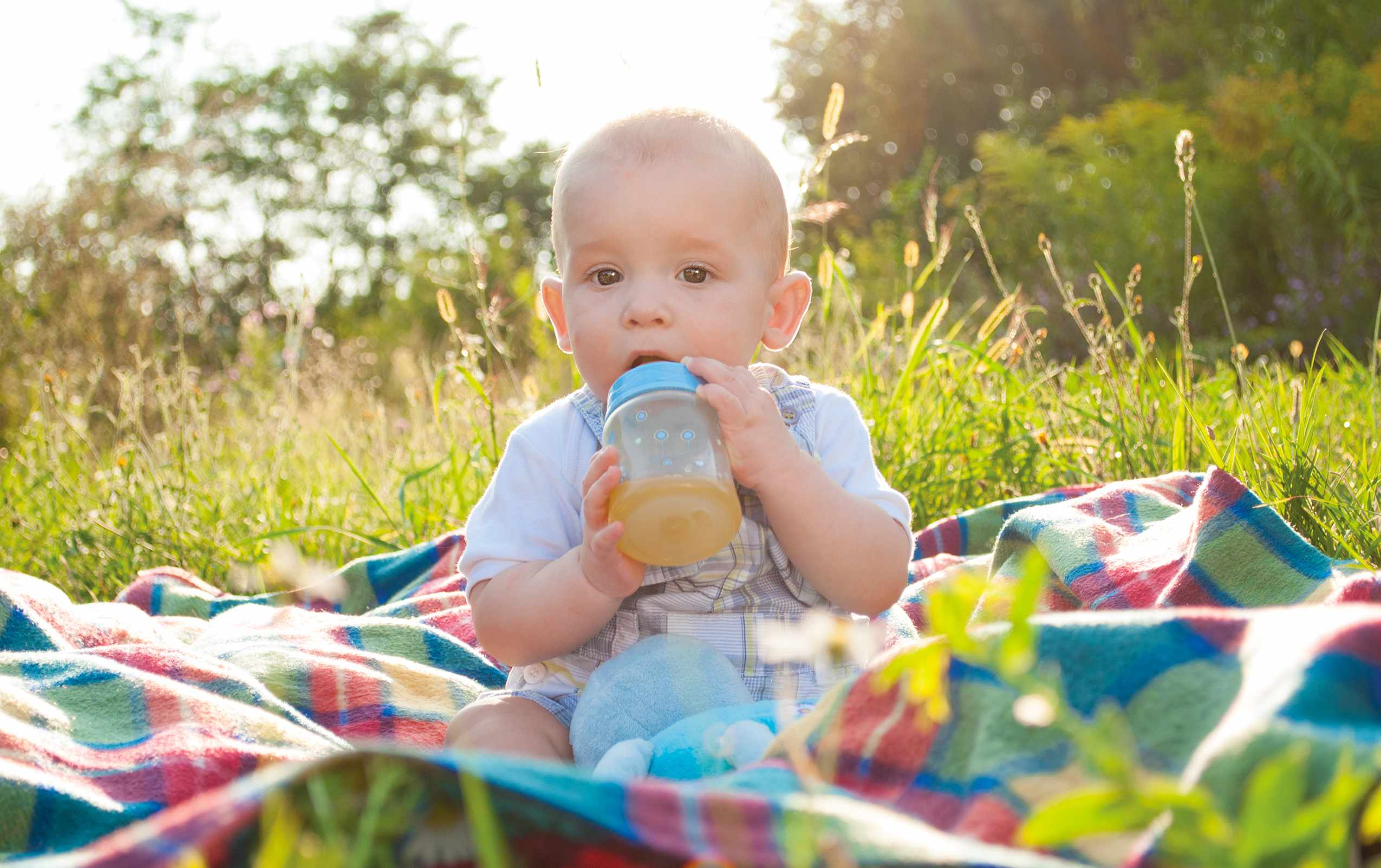a baby sitting outsde on a blanket drinking from a juice bottle