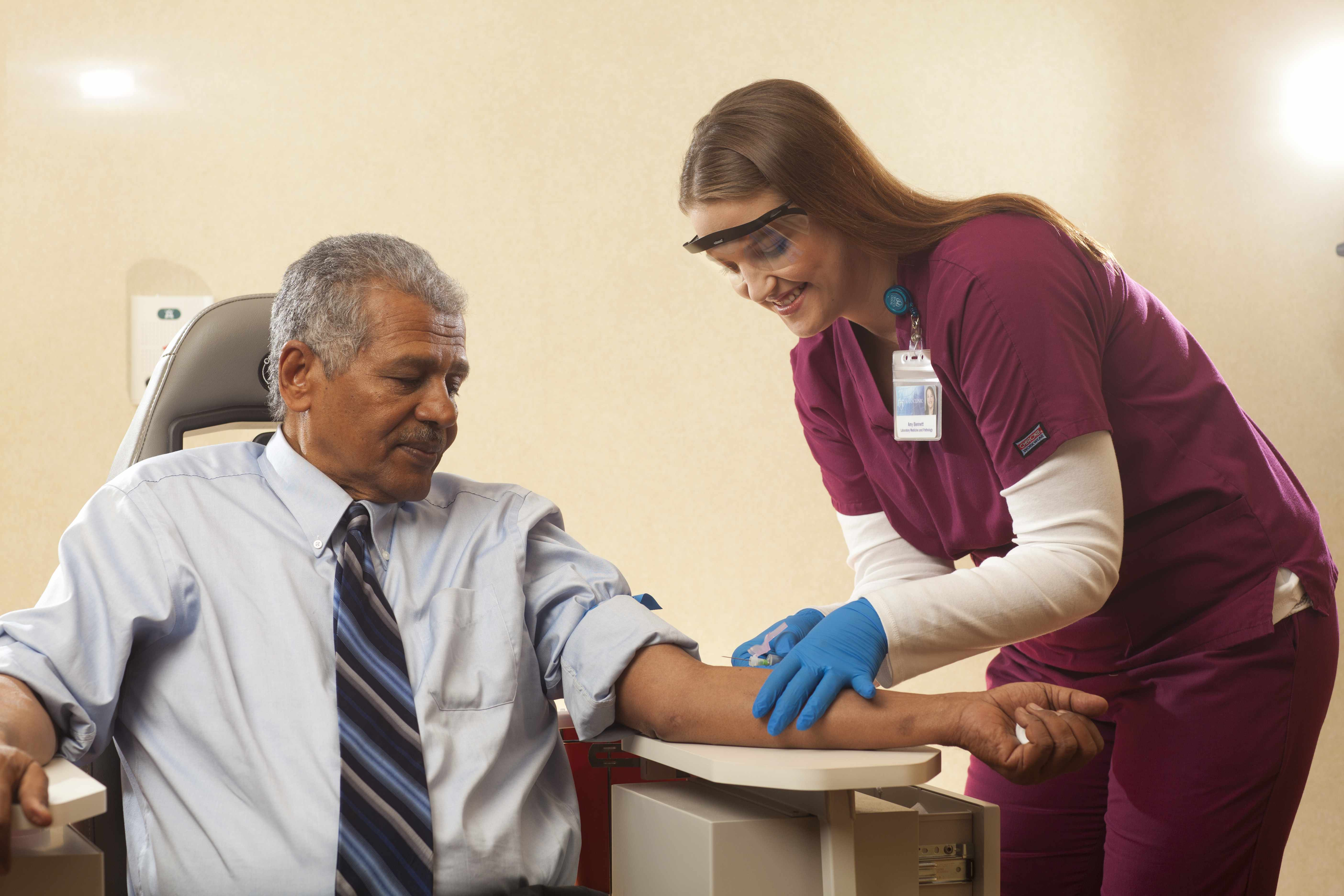phlebotomist drawing blood from patient
