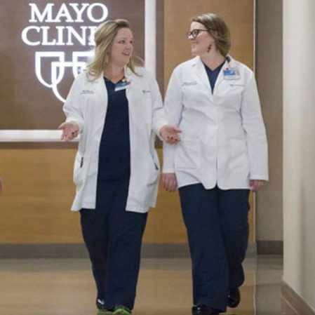 Mayo Clinic staff, two women, walking in the hallway and talking in a walking meeting