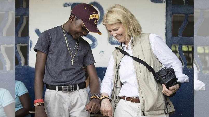 patient from Liberia, Sampson, walking and smiling with Greta Van Susteren