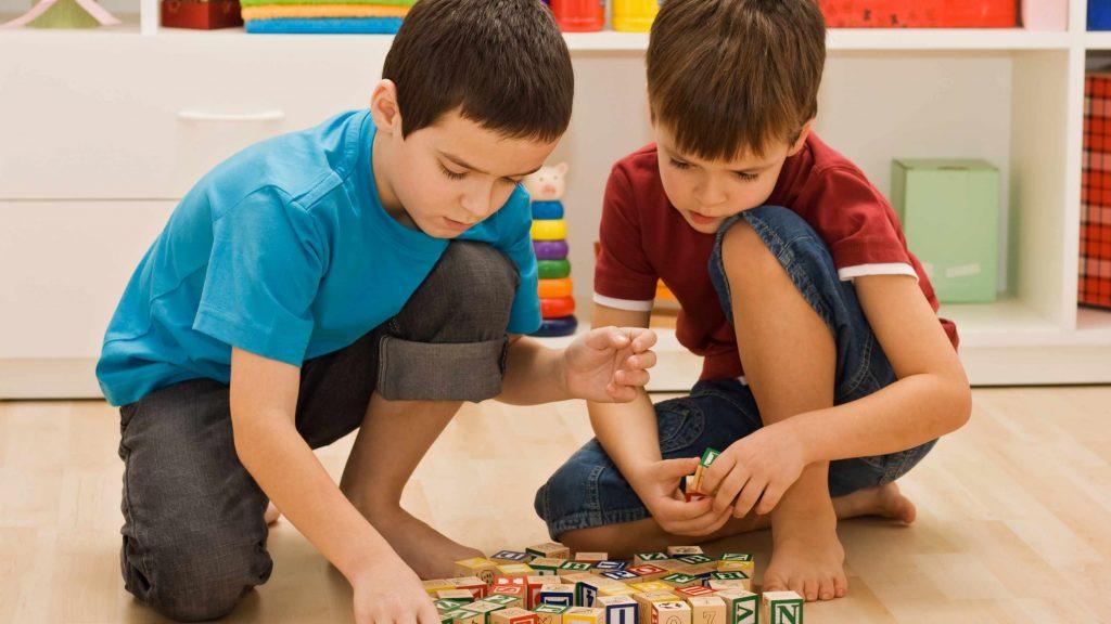 Dos niños pequeños juegan con bloques en el piso