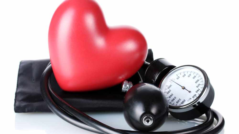 a blood pressure cuff and gauge, with a red plastic valentine heart
