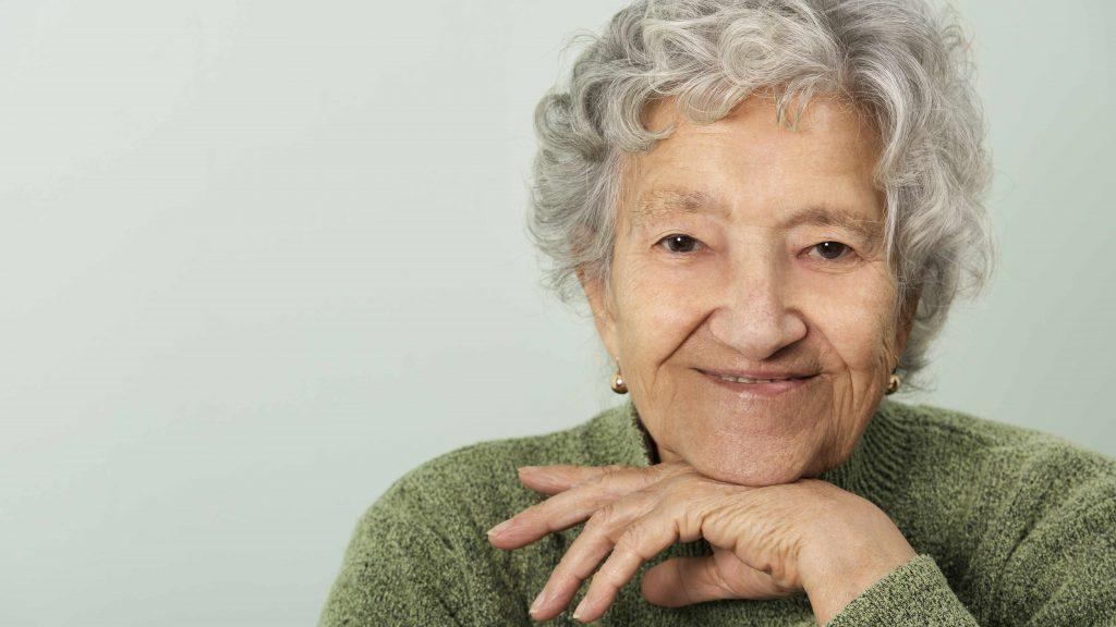 Acercamiento de una anciana feliz y sonriente, con la mano en el mentón