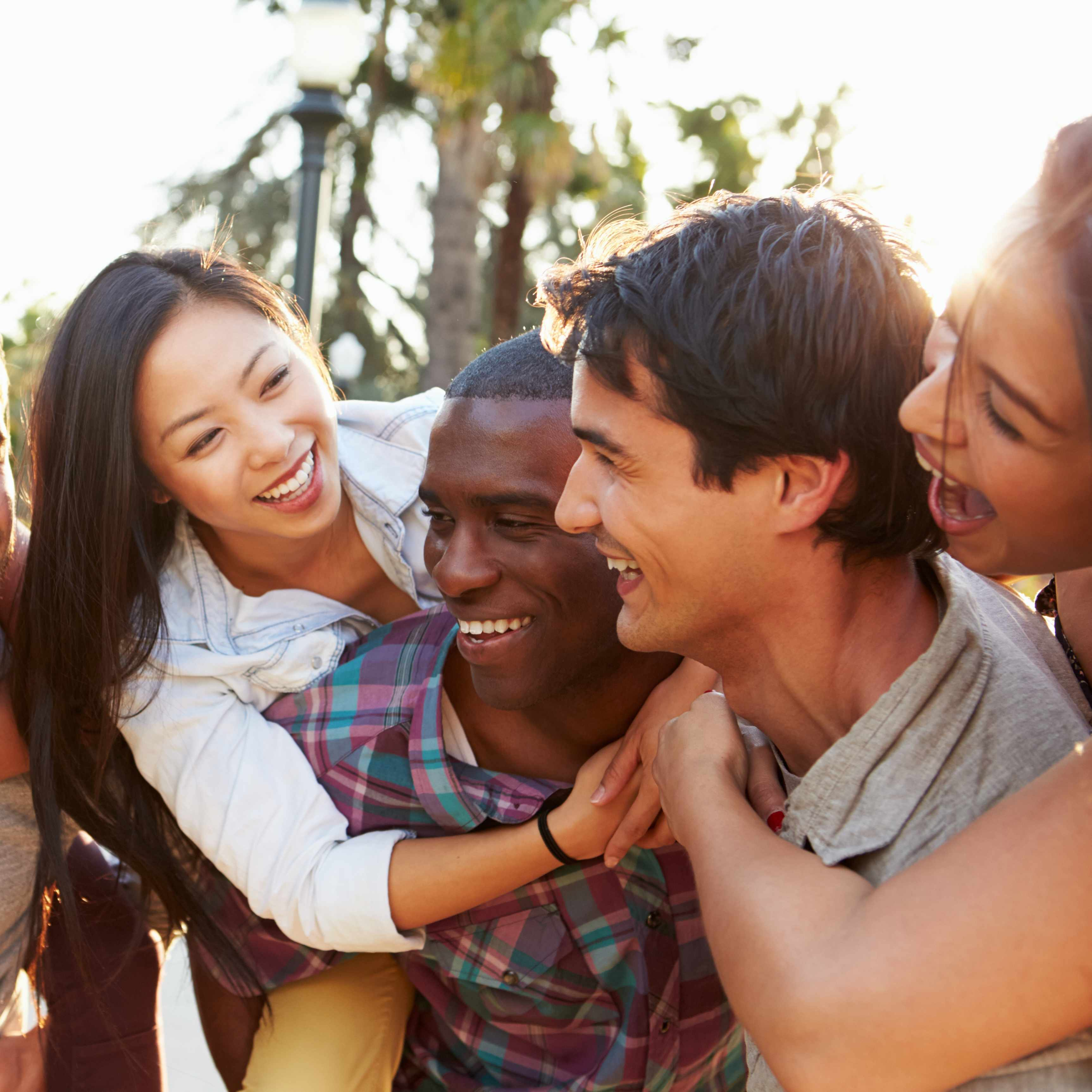 a diverse group of young people hugging and laughing, having fun