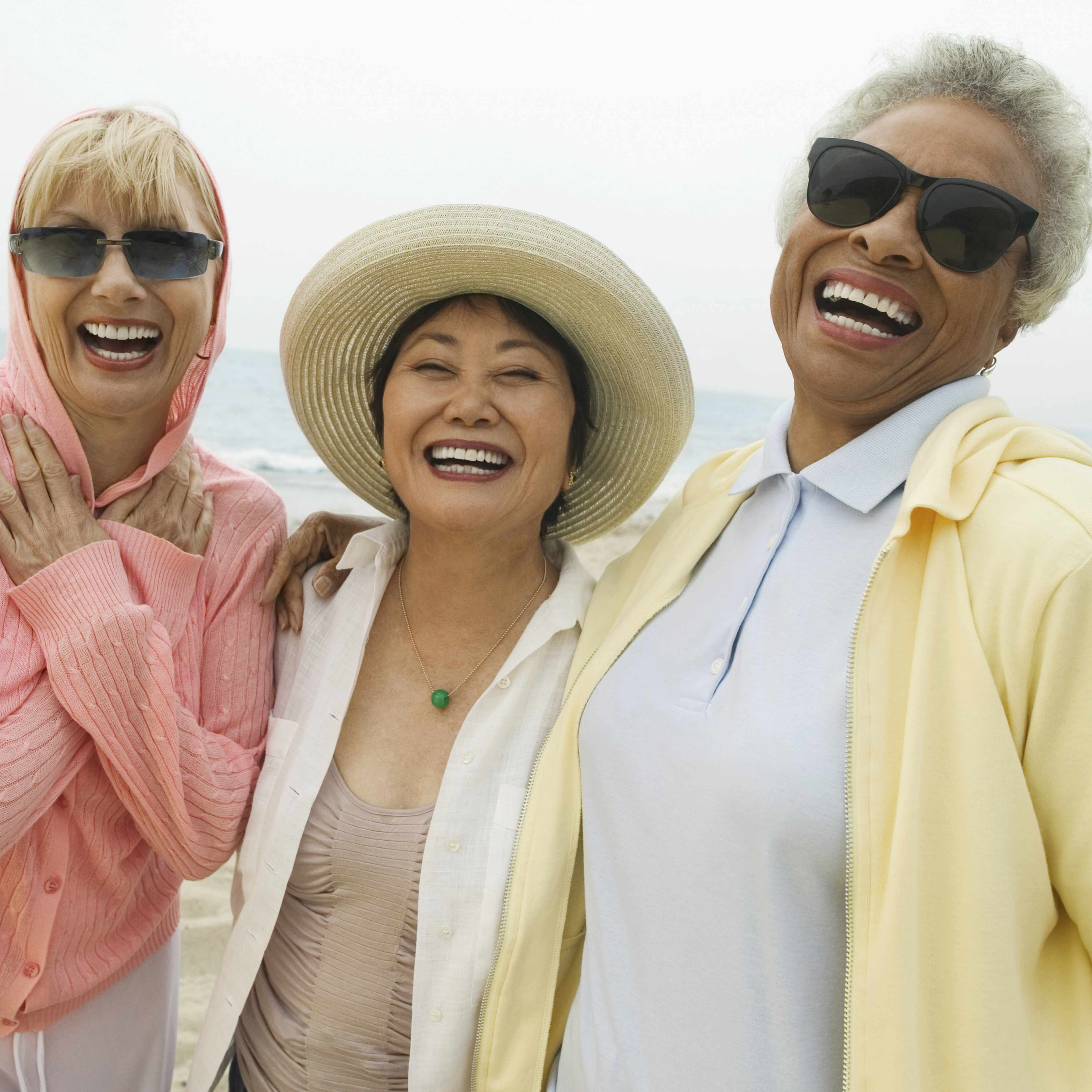 a group of diverse, middle-aged women friends walking on the beach and laughing