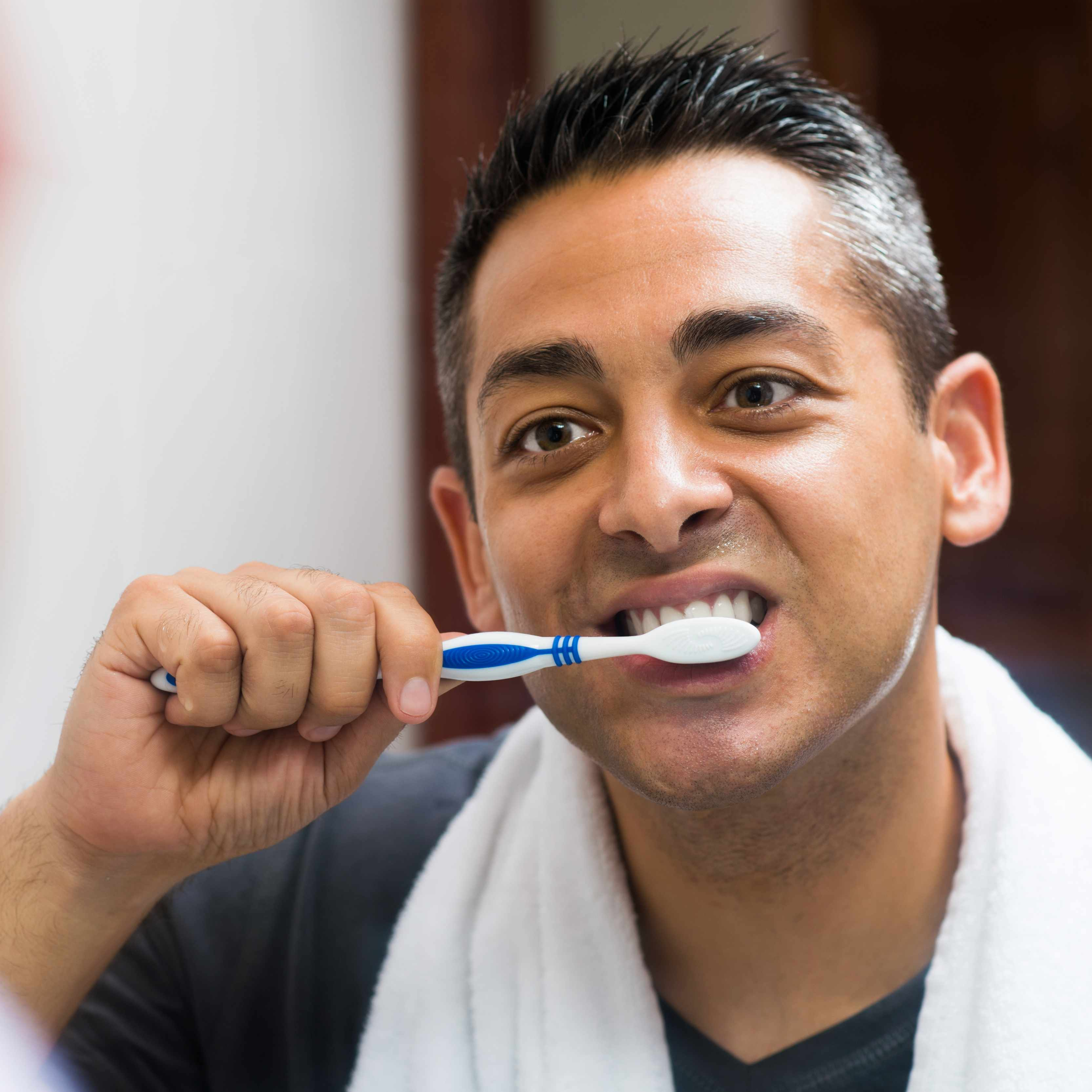 a man looking in a bathroom mirror and brushing his teeth