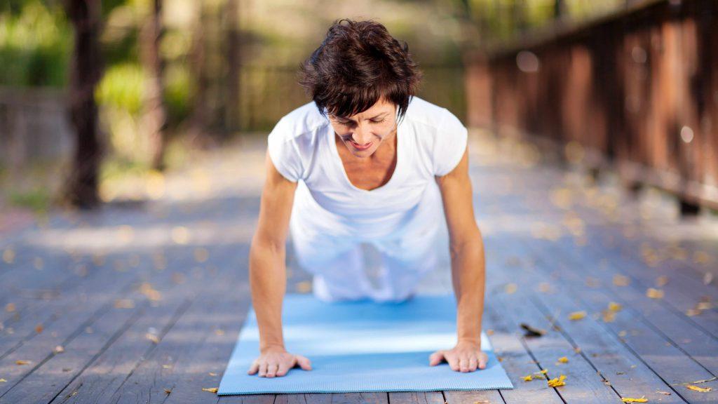 Mujer de mediana edad sobre una colchoneta de yoga en pleno ejercicio y estiramiento