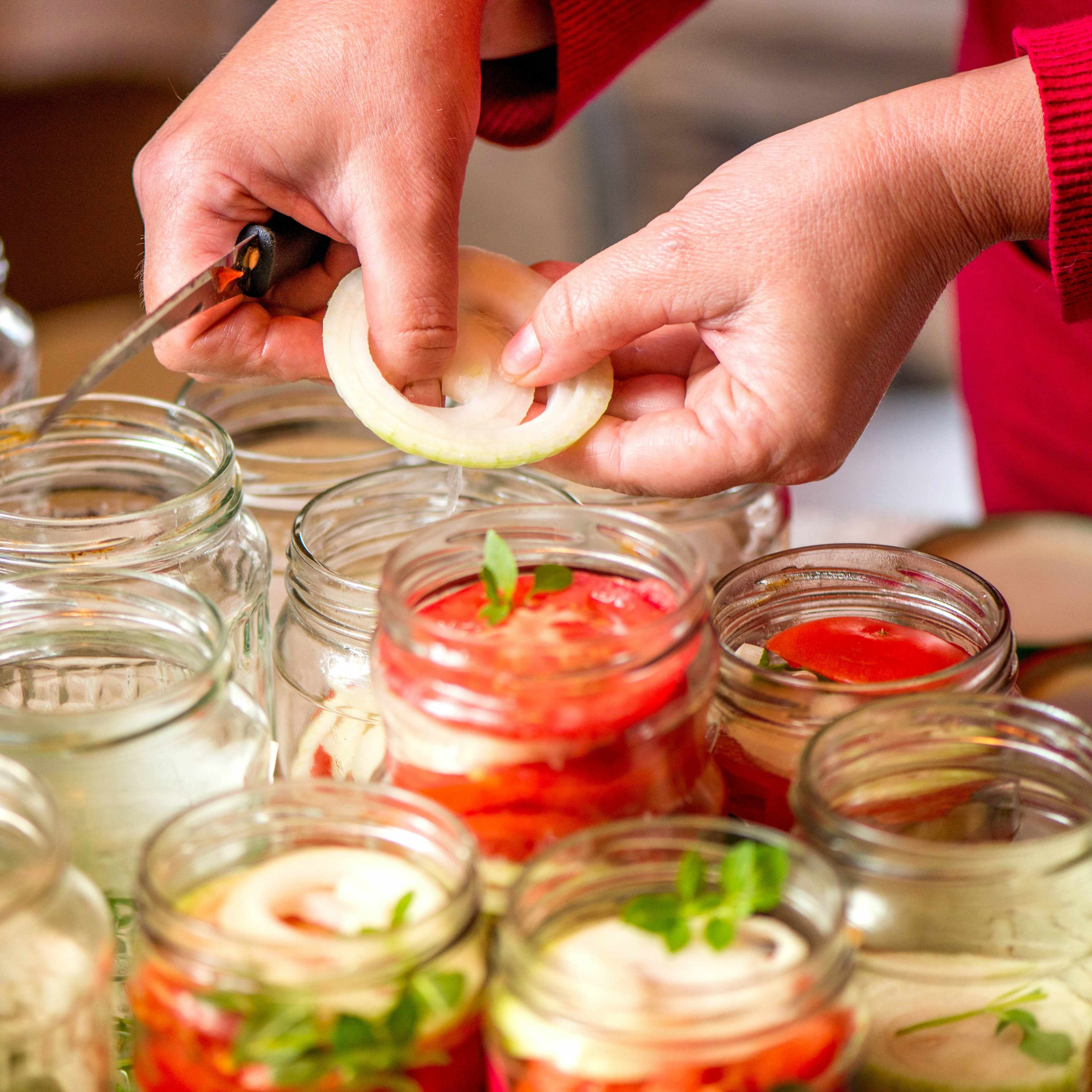 a person canning vegetables in jars