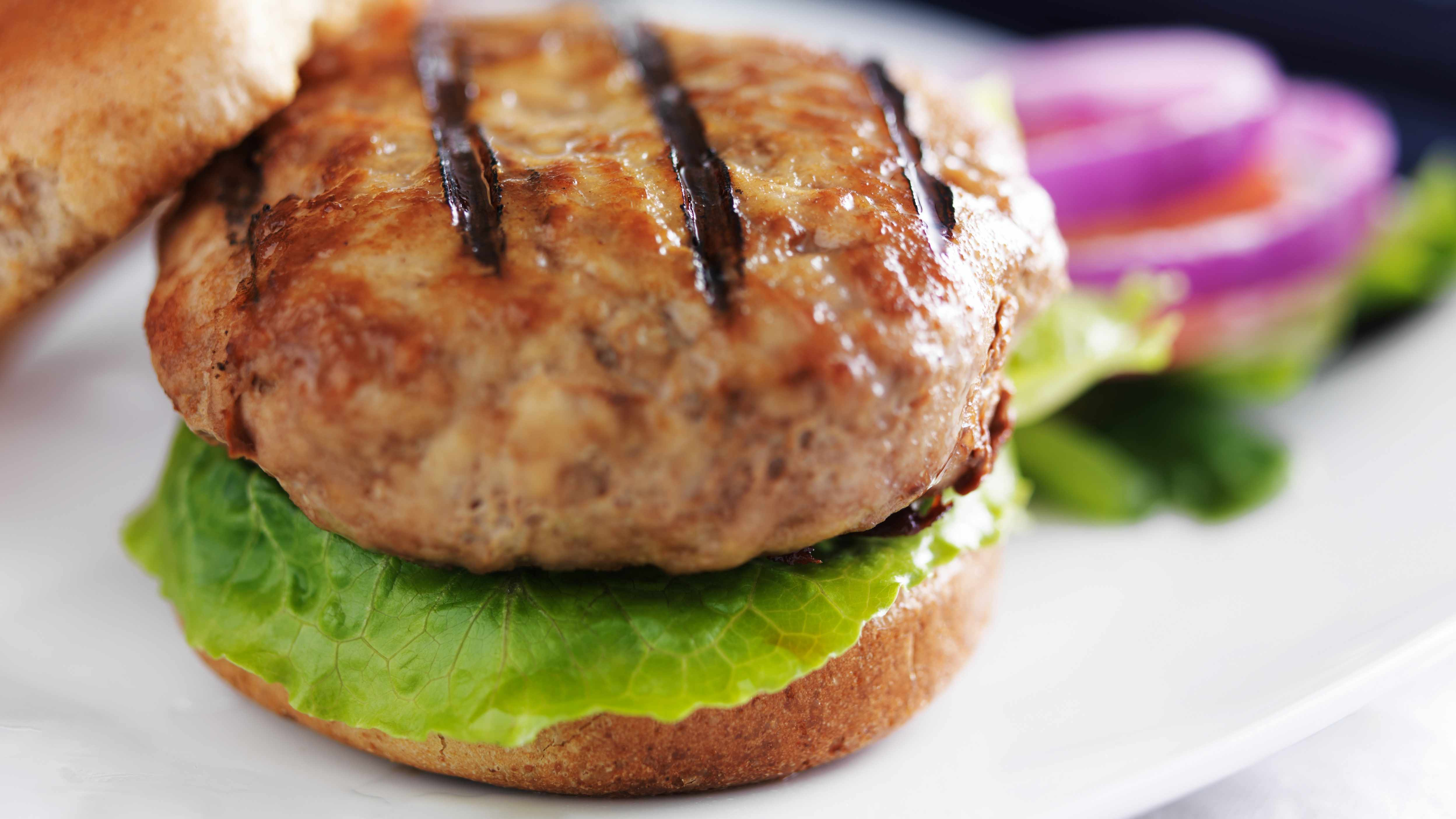 a turkey burger on a bun with lettuce and onions