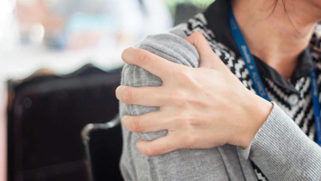 Una mujer sostiene su hombro adolorido