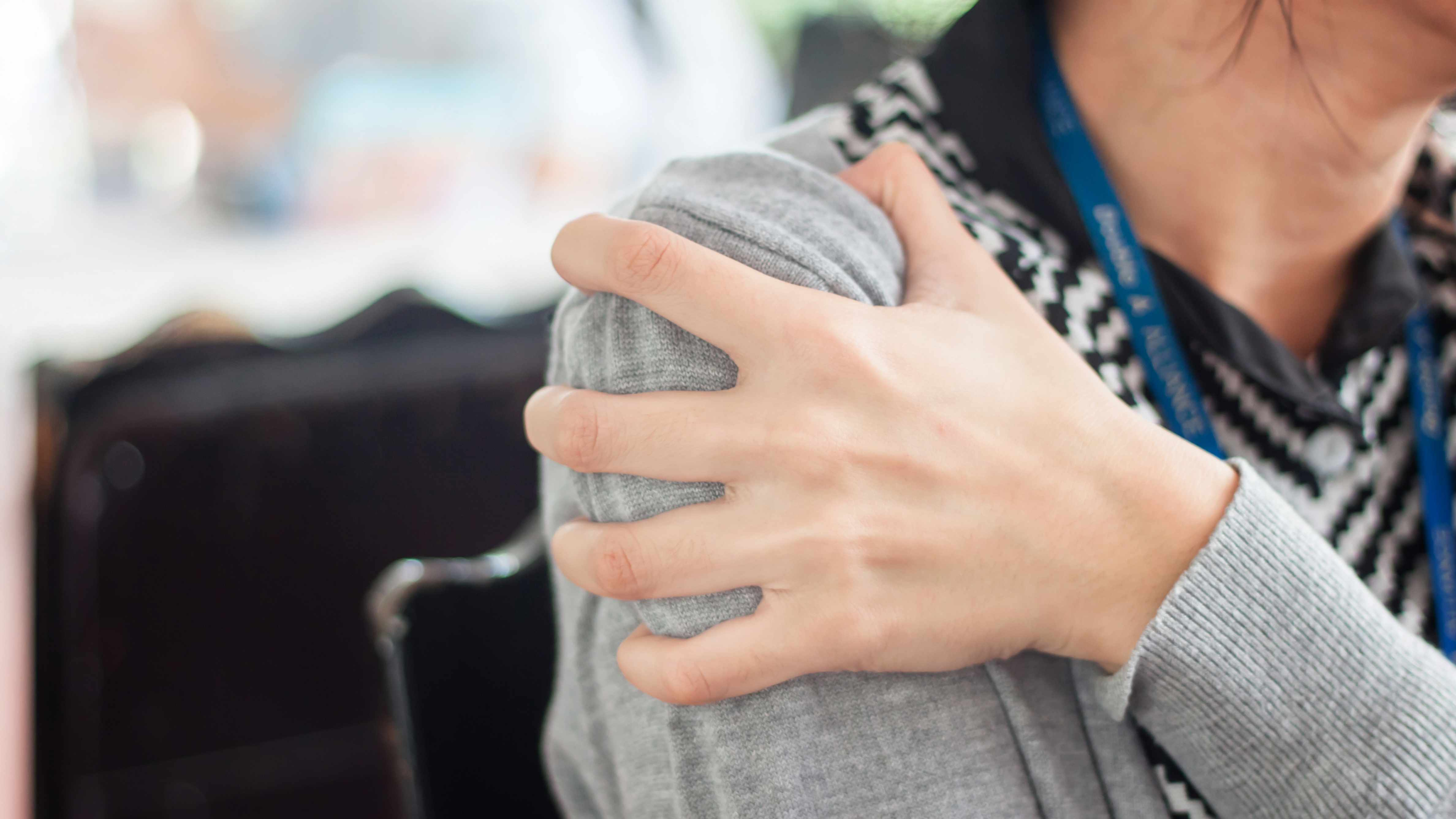 a woman in pain holding her shoulder