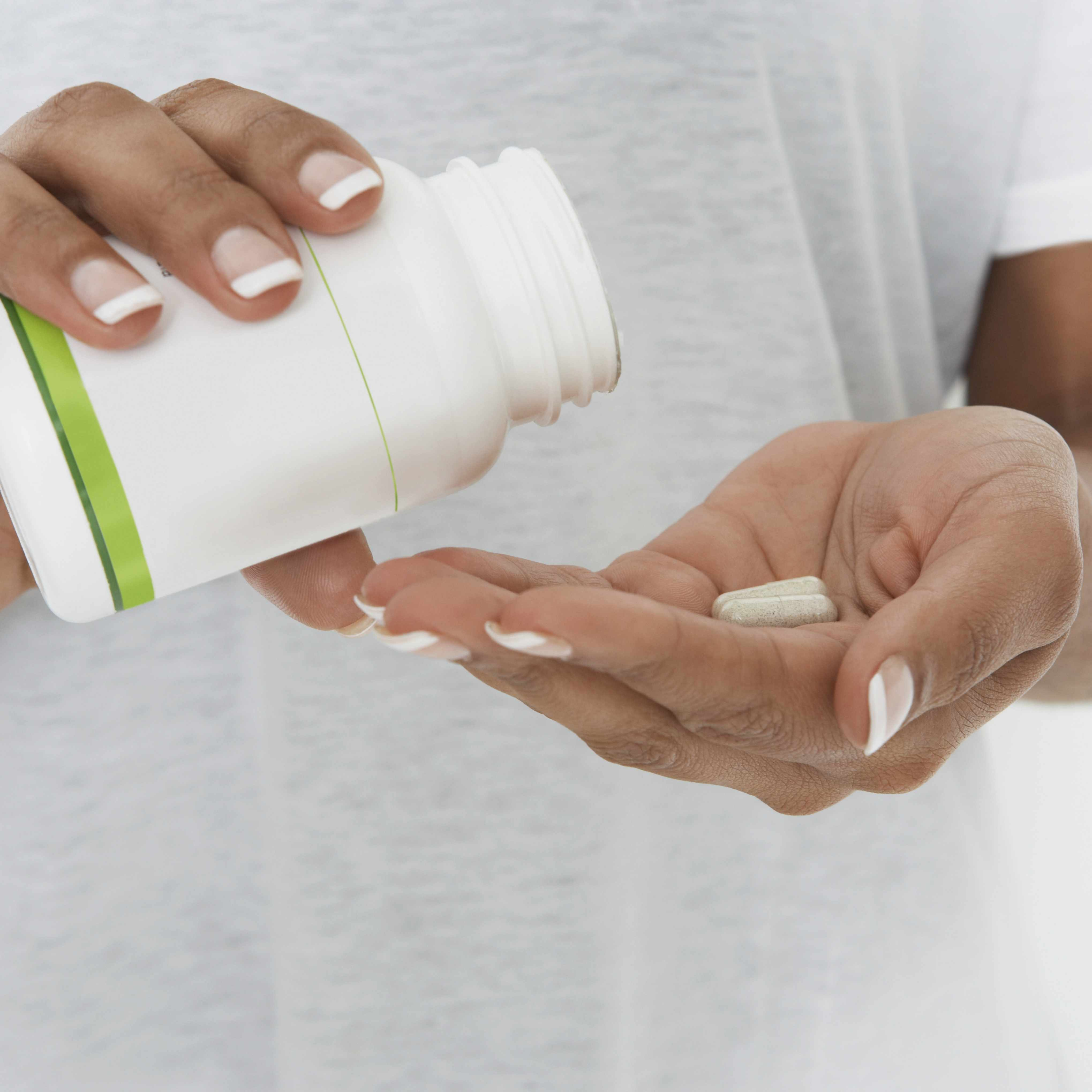 a woman pouring pills from a bottle into her hand