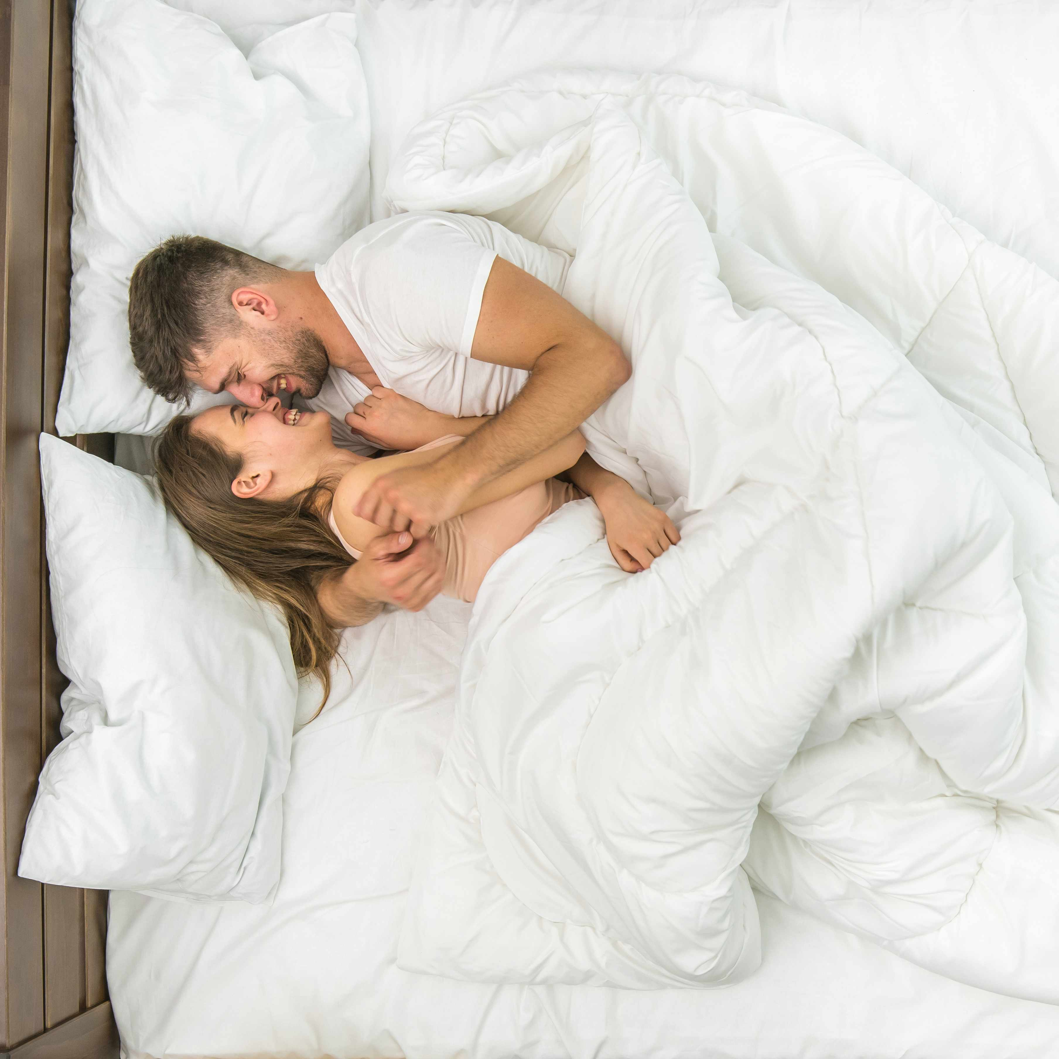 a young couple lying in bed, surrounded by white sheets and comforter, holding and hugging each other