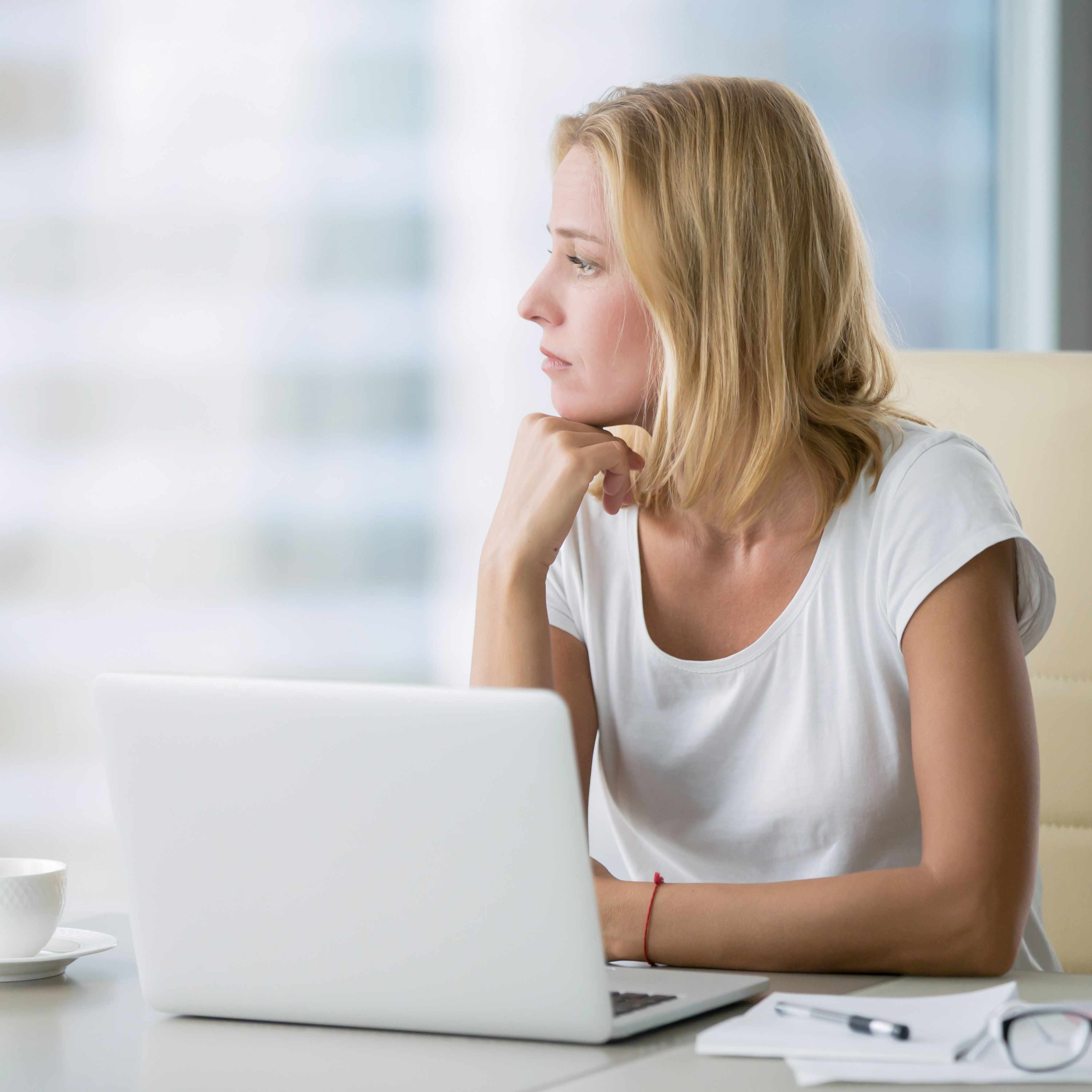 a young woman sitting at a desk with a computer looking thoughtfully out a window, perhaps sad