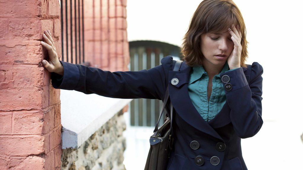 Una mujer joven se apoya sobre una pared con una mano, mientras que con la otra se sostiene la frente y luce mareada o aturdida