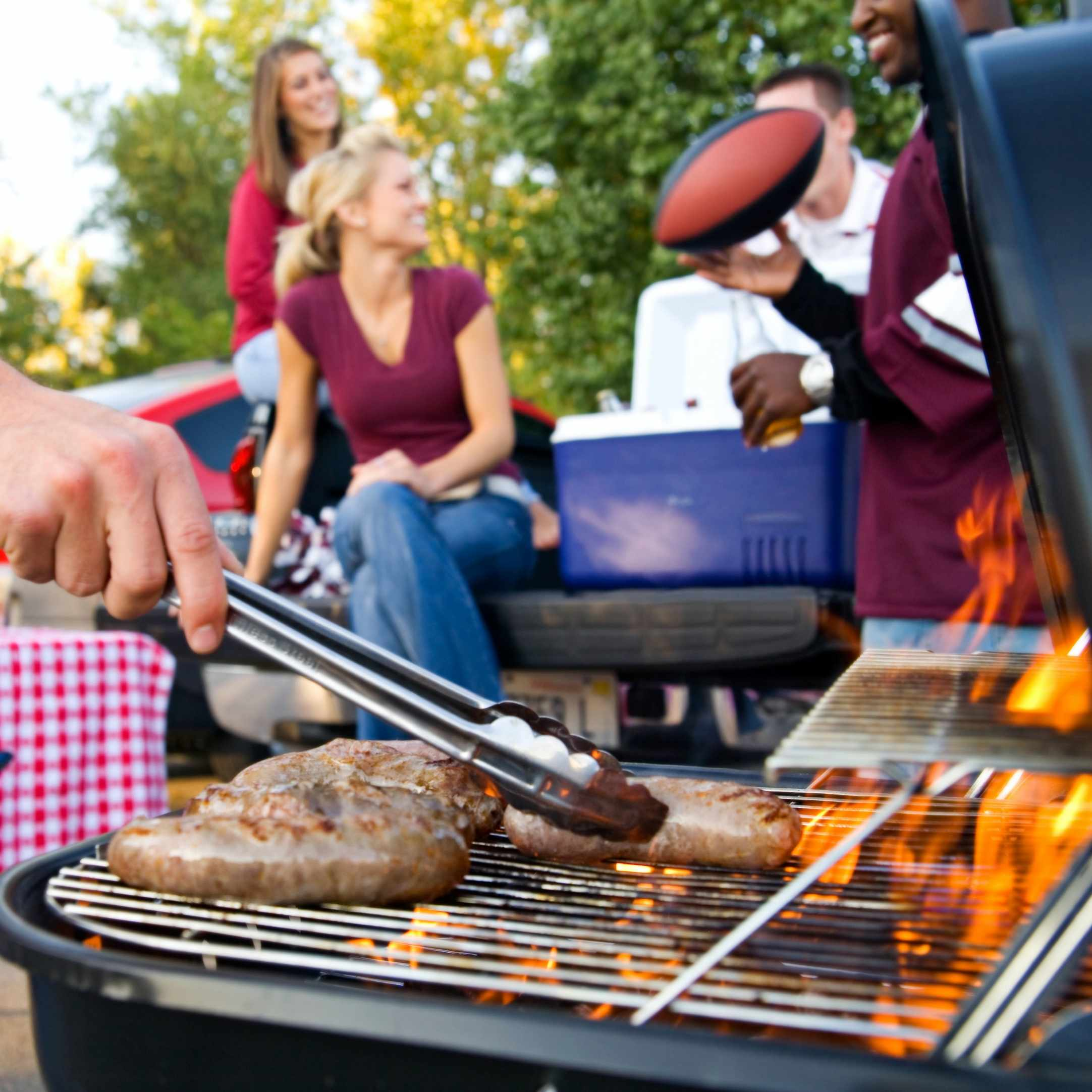 a group of friends grilling outside for a picnic