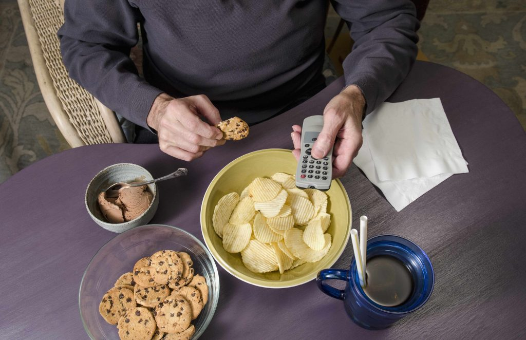 man sitting at table overeating, eating junk food, poor nutrition, binge eating, remote, TV