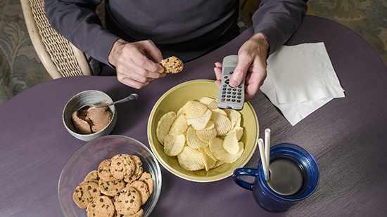 Un hombre sentado a la mesa come en exceso comida chatarra, que es mala nutrición, y se da un atracón, mientras sostiene el control remoto del televisor.