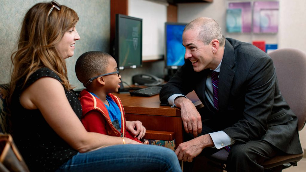 Un médico le sonríe a un paciente pediátrico que está con su madre