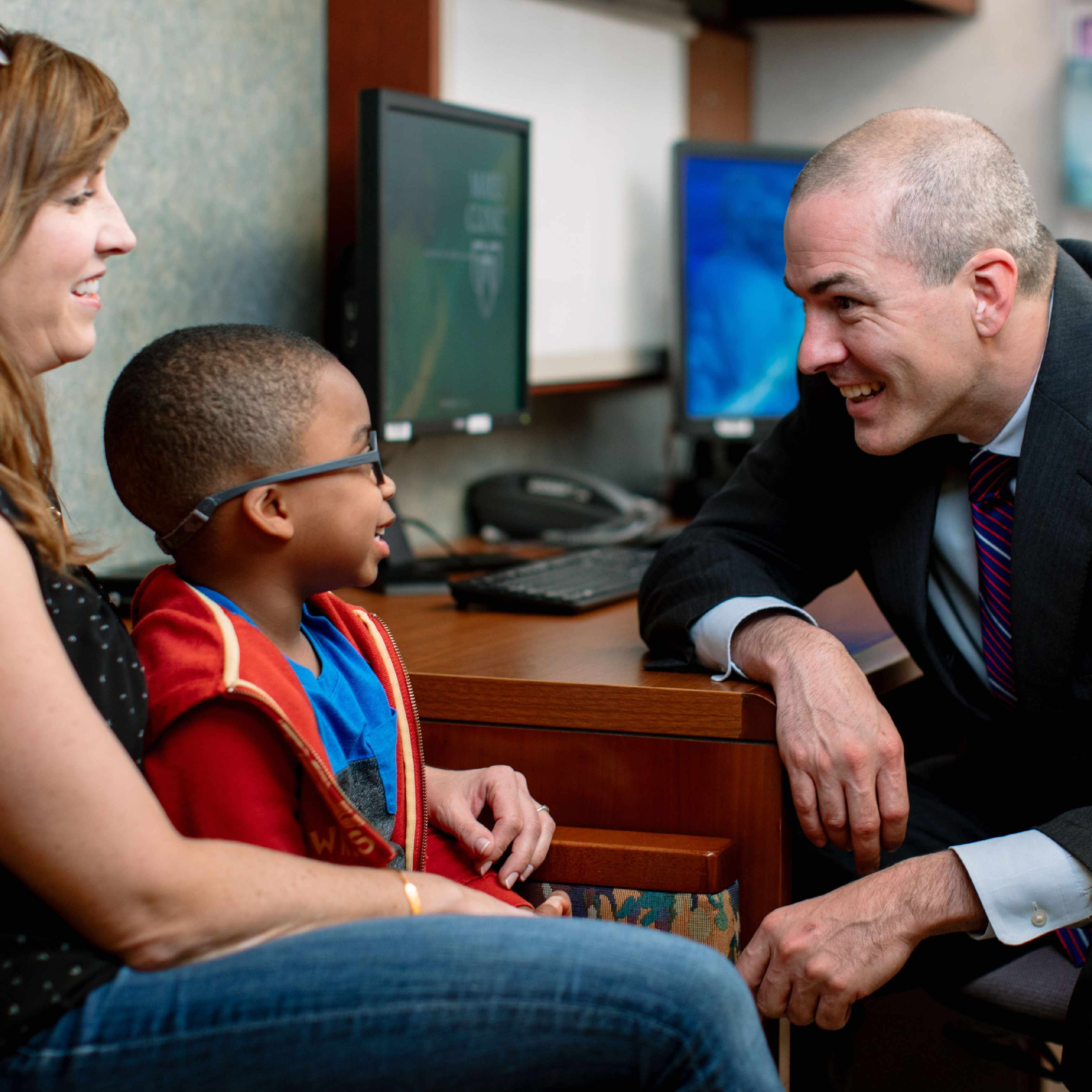 physician smiling at pediatric patient and mother