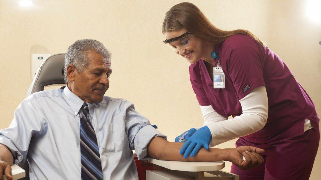 Una flebotomista le extrae sangre a un paciente.