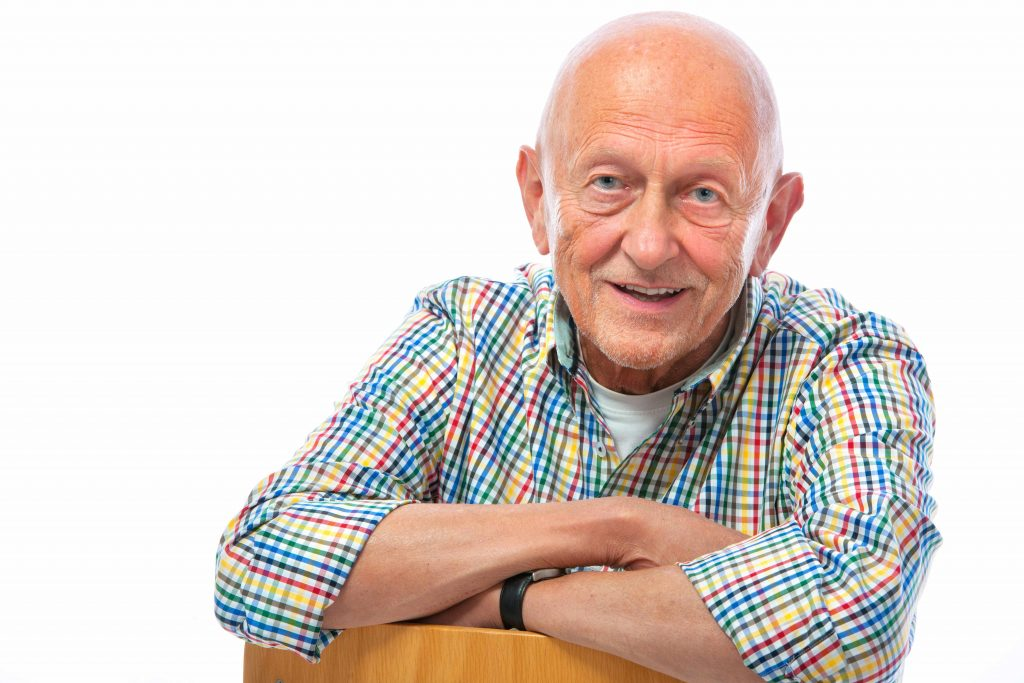a close-up of a bald, friendly-looking older man in a plaid shirt