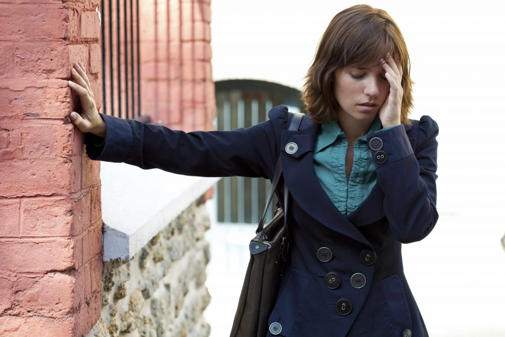 a young woman standing outside, with one hand on a wall and the other up to her forehead, looking dizzy or light-headed