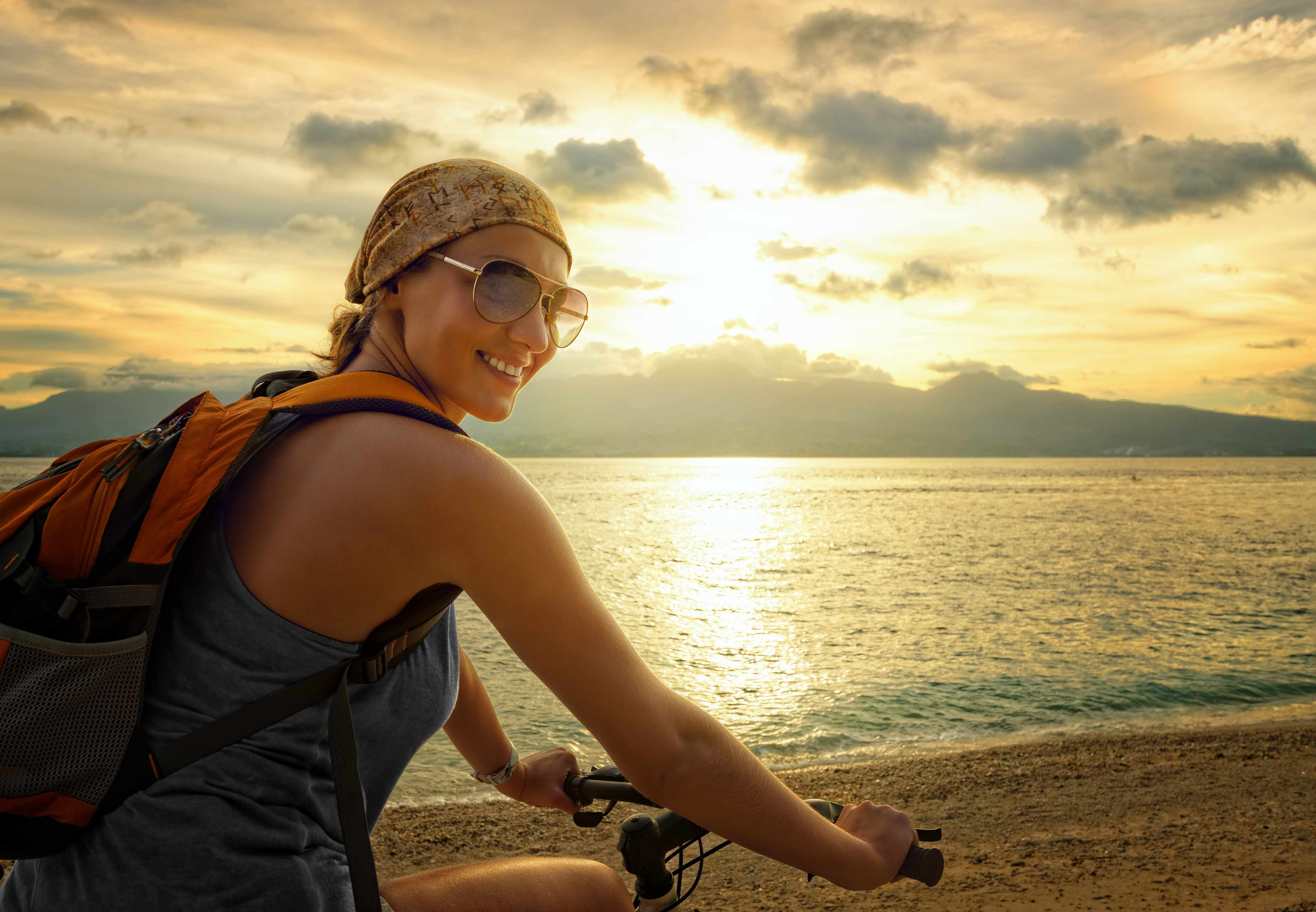 a young woman riding a bicycle along the beach or lake shore with the sun setting