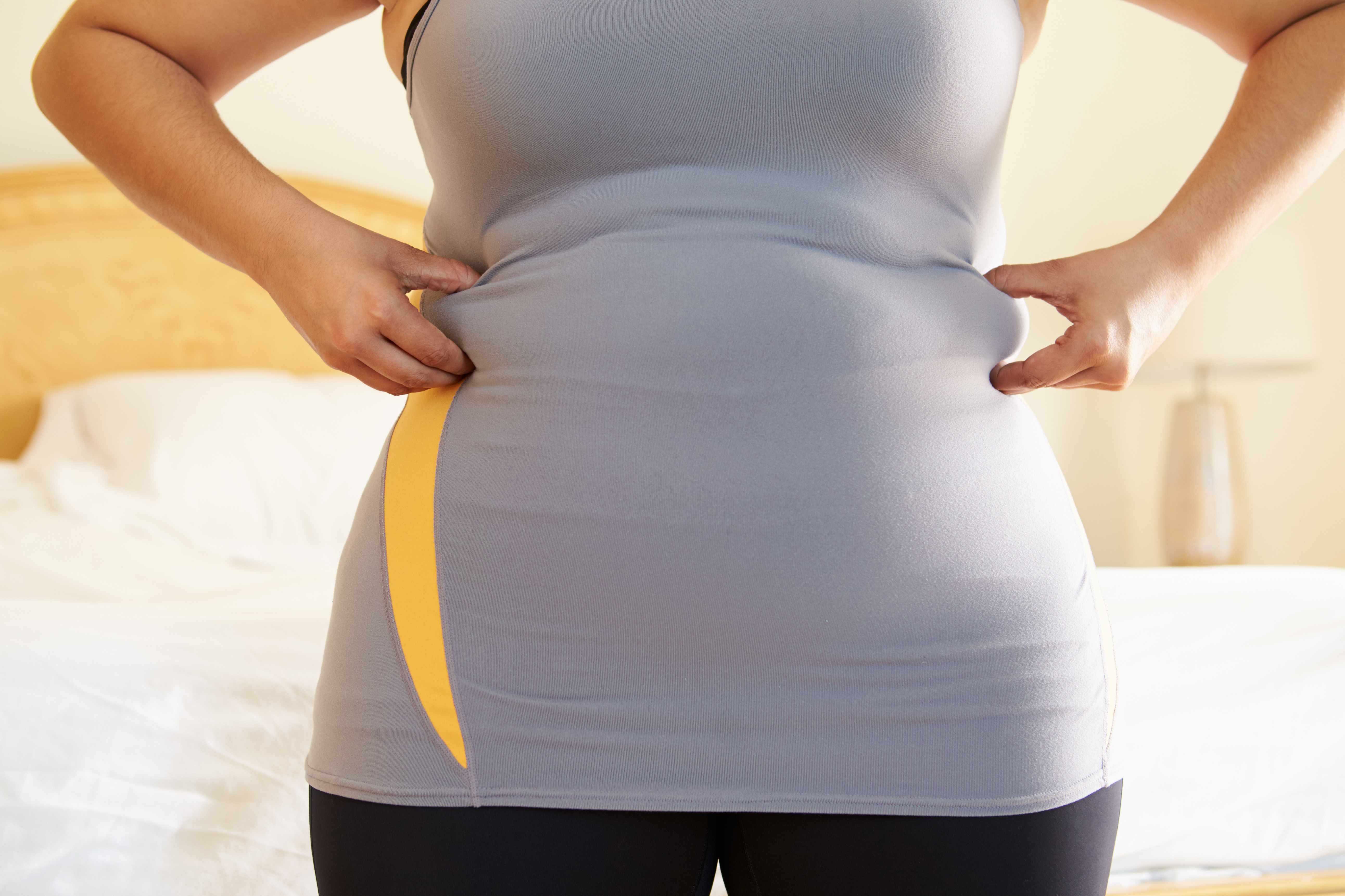 a woman measuring her waist and stomach looking for fat, concerned about weight gain