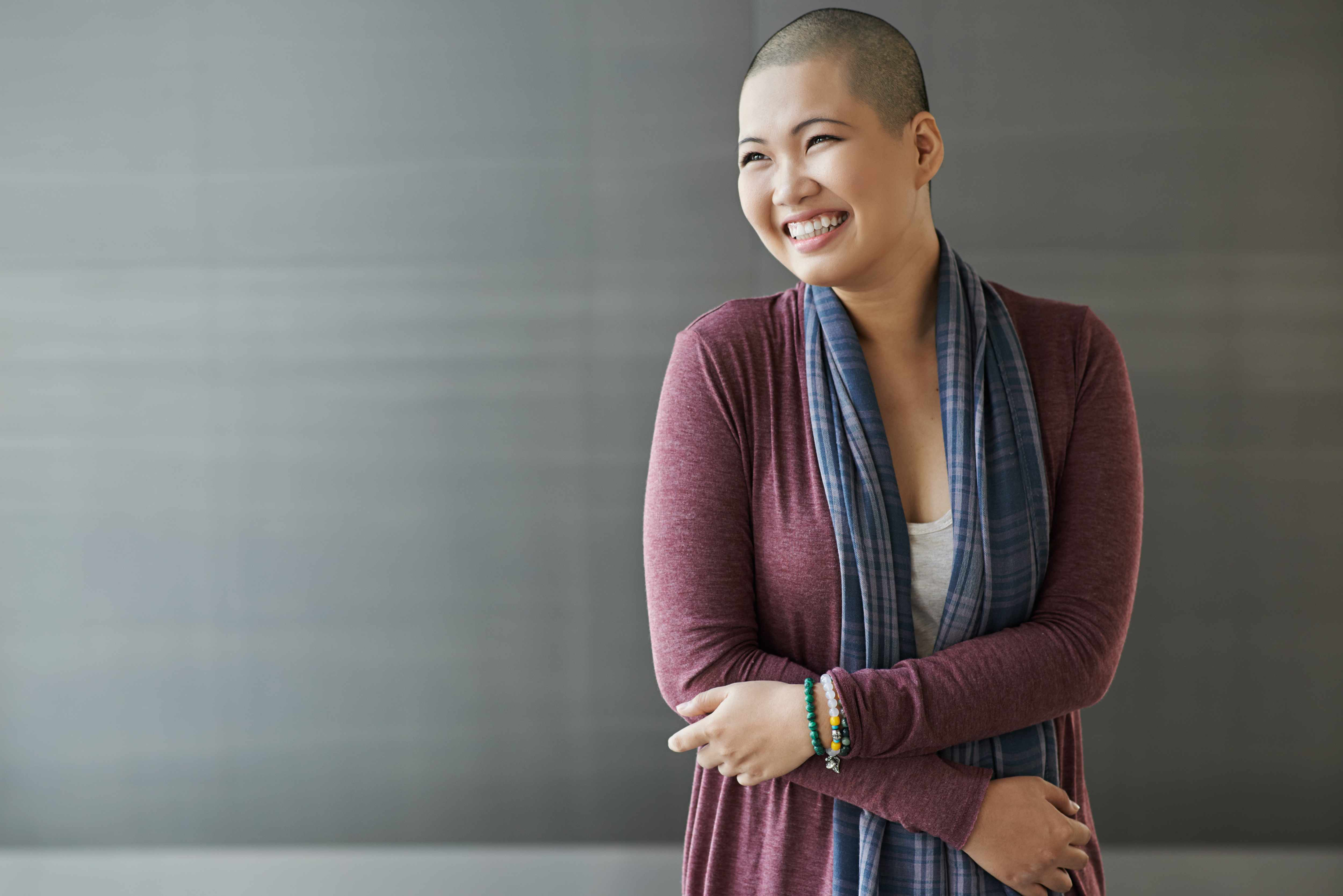 a smiling young Asian woman with shaven head representing cancer patient after chemo therapy