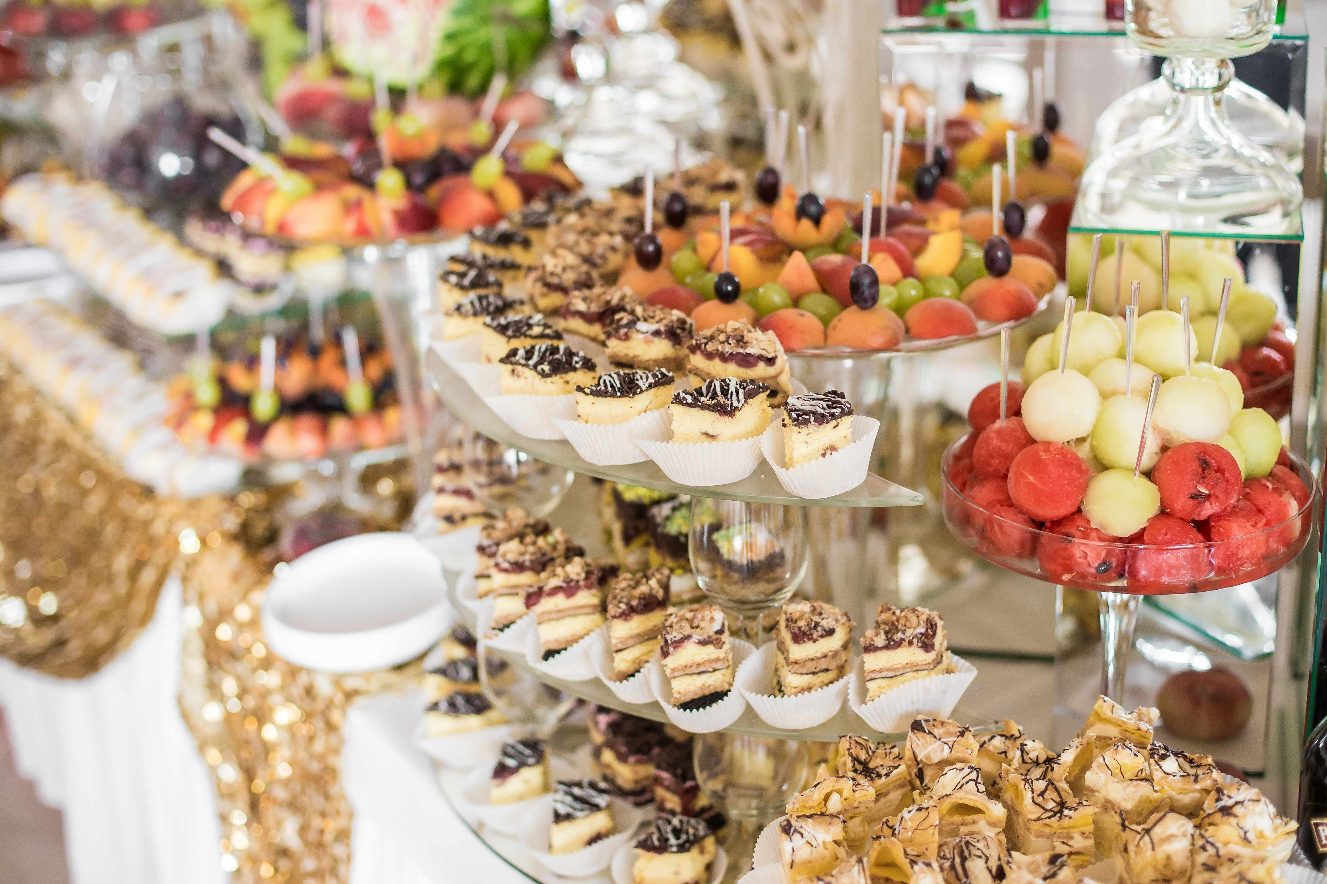 food table at a reception filled with fruits and pastries