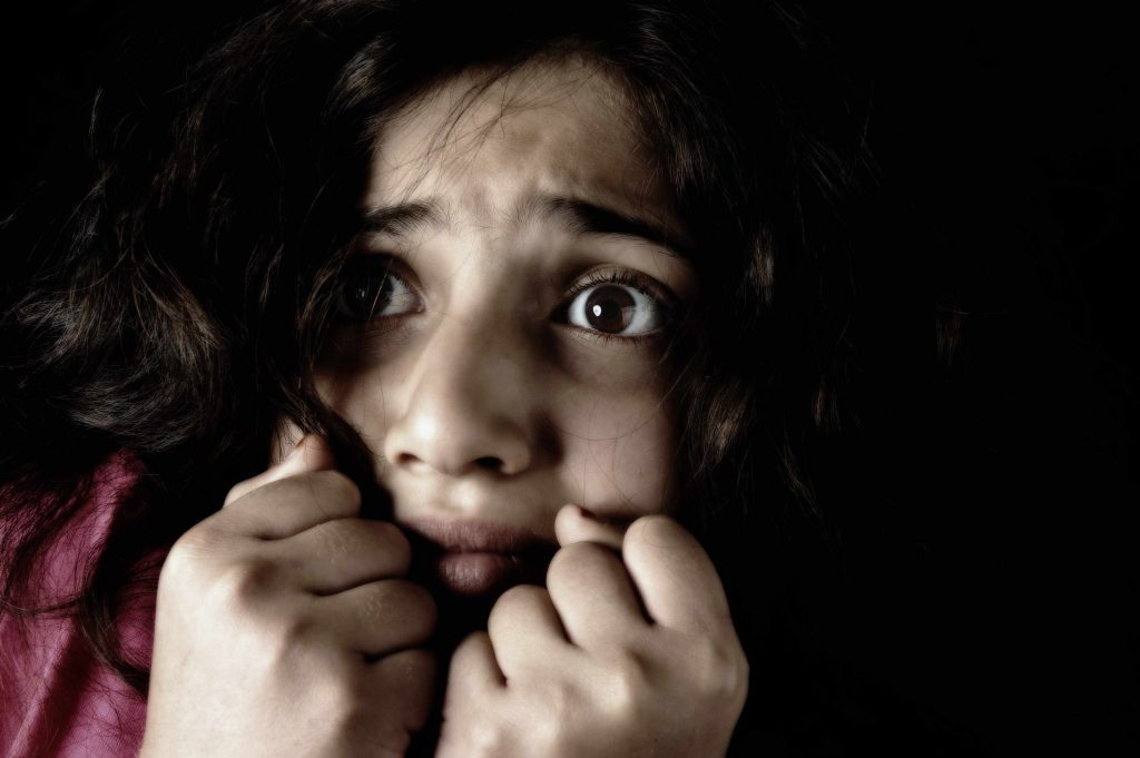 a wide-eyed, scared young girl in a dark room