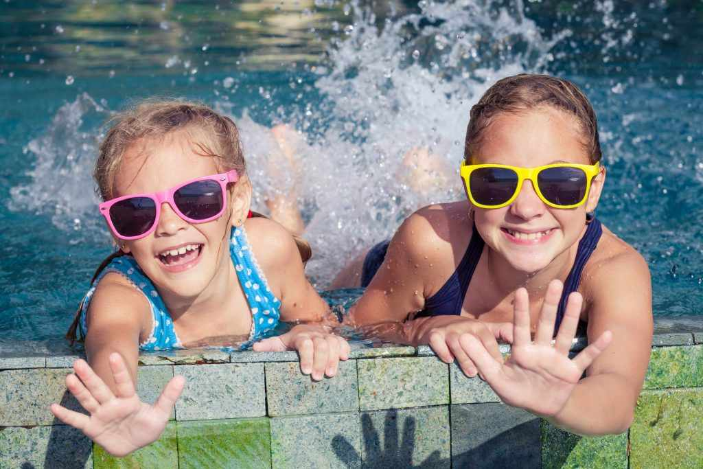 Two girls splashing in a swimming pool, wearing sunglasses