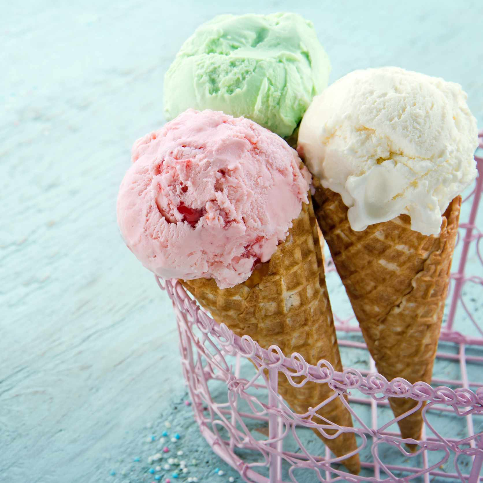 three ice cream cones in a wire basket rack