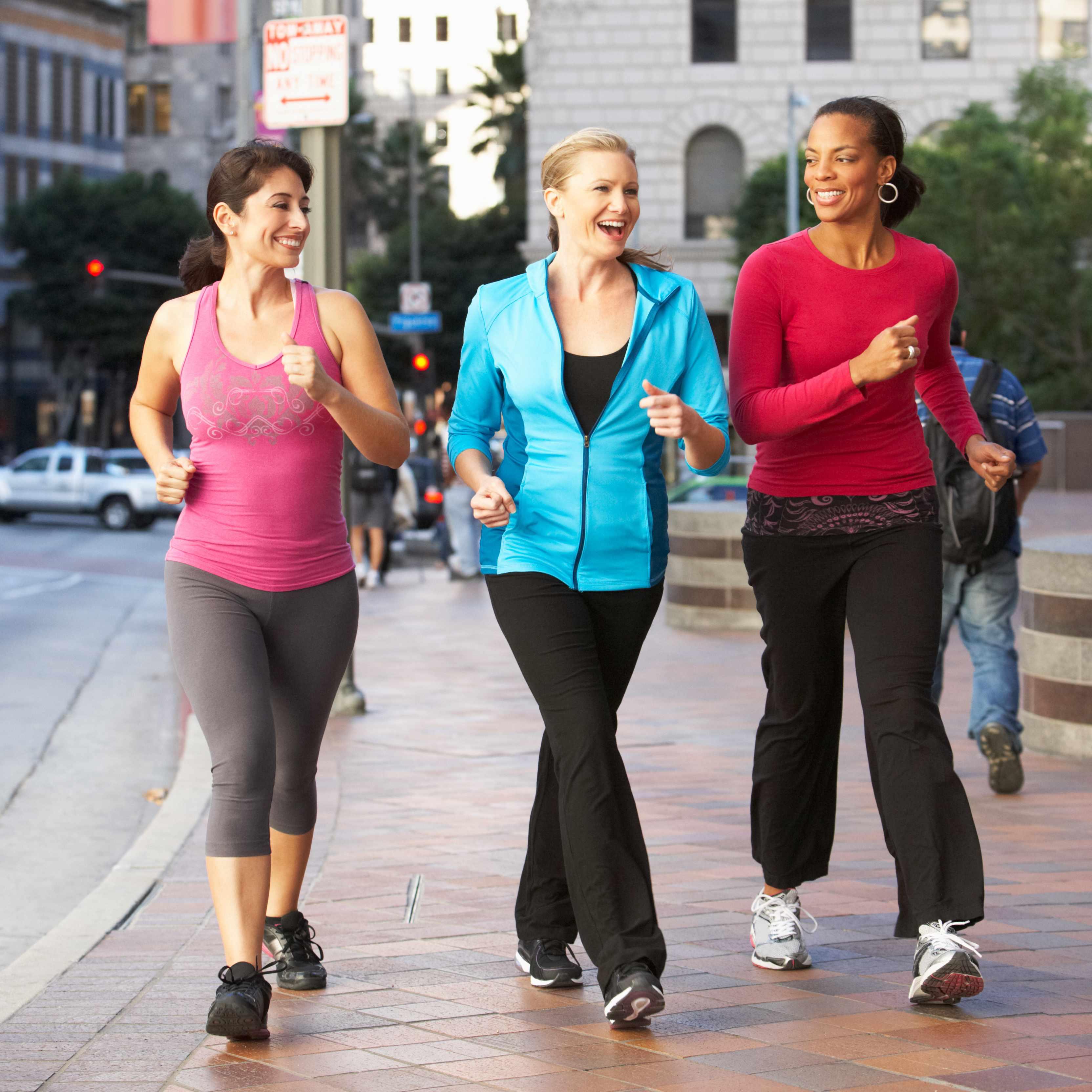 three smiling young women walking vigorously along a city sidewalk