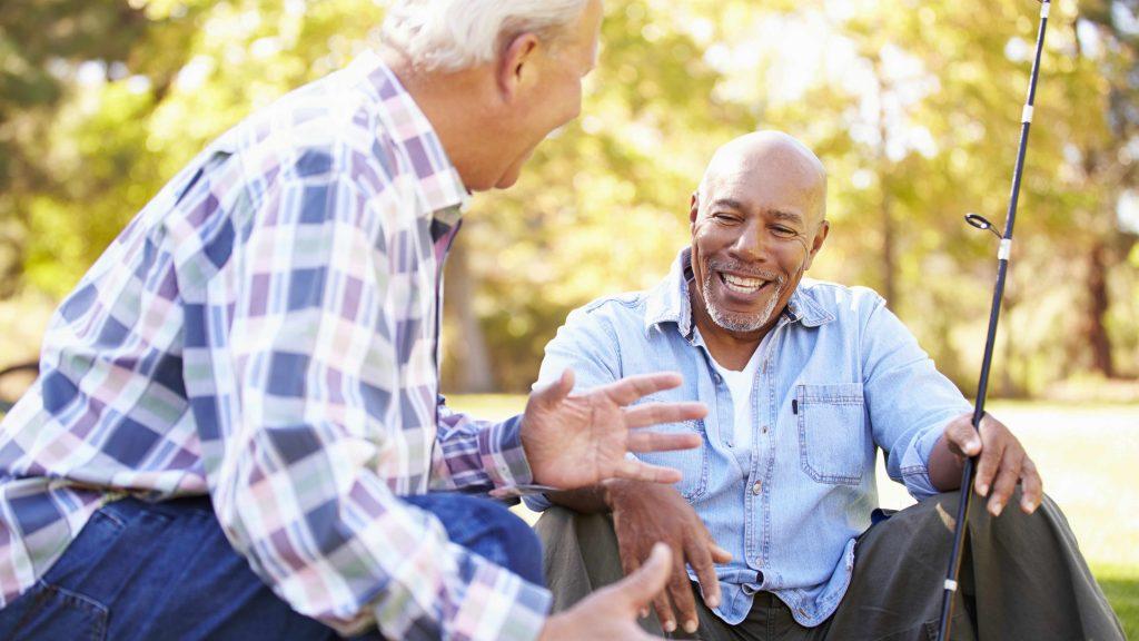 Dos hombres de mediana edad ríen y sonríen mientras pescan
