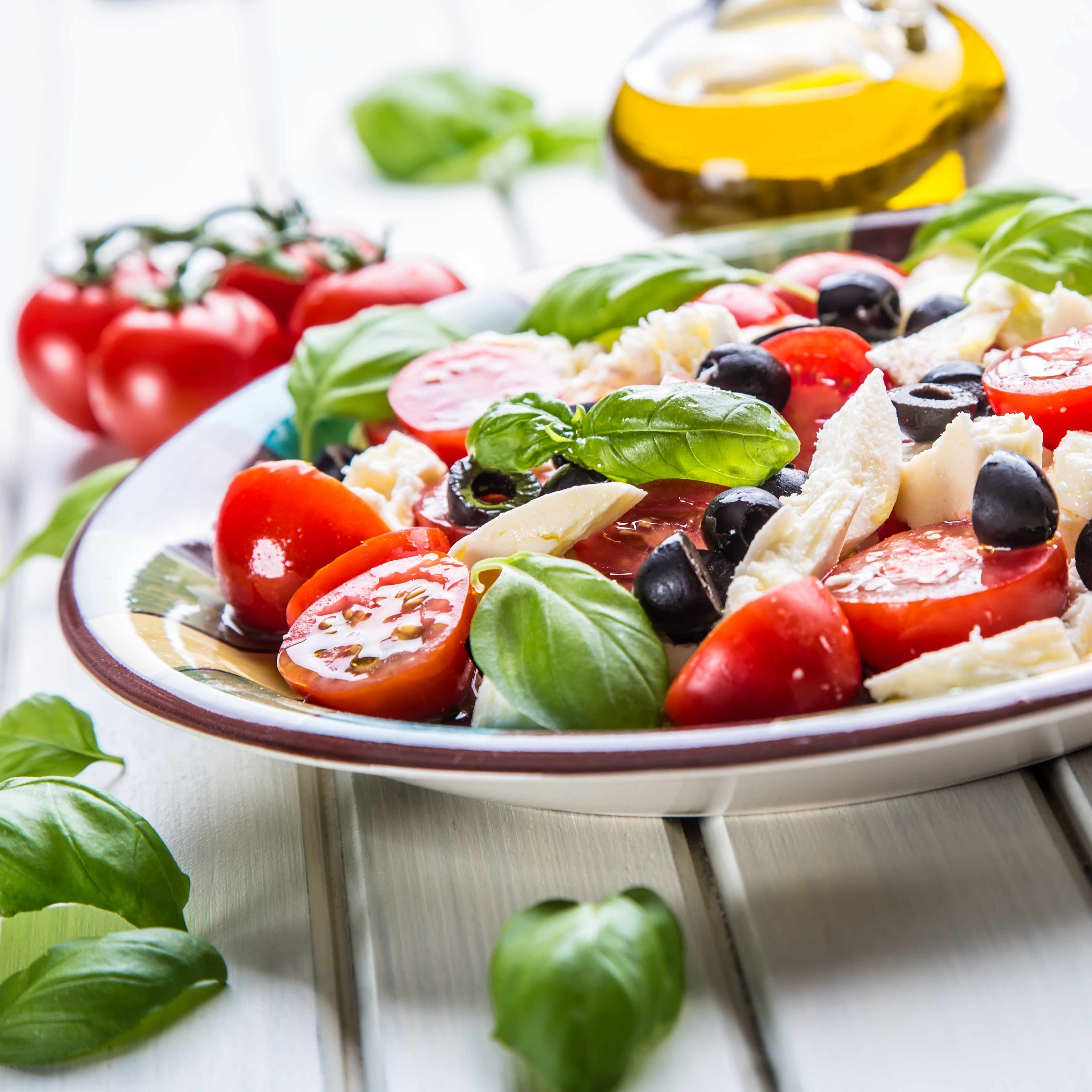 Mediterranean diet salad with tomatoes basil leaves, olives and fish