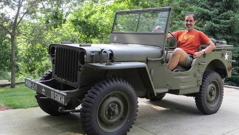 Mayo Clinic cardiologist Gurpreet Sandhu, M.D., Ph.D. in a WWI jeep he refurbished