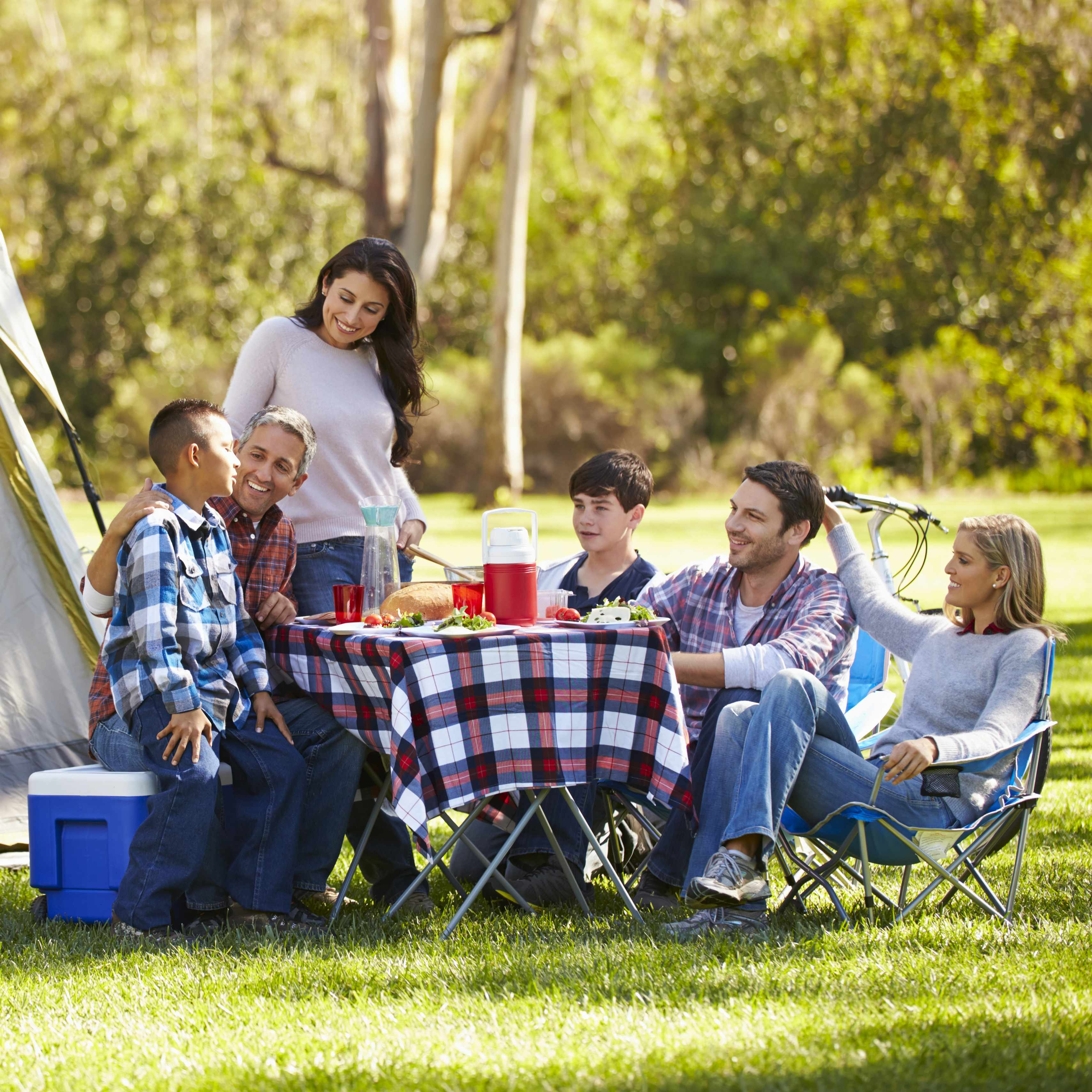 a family with friends outside camping and having an outdoor picnic