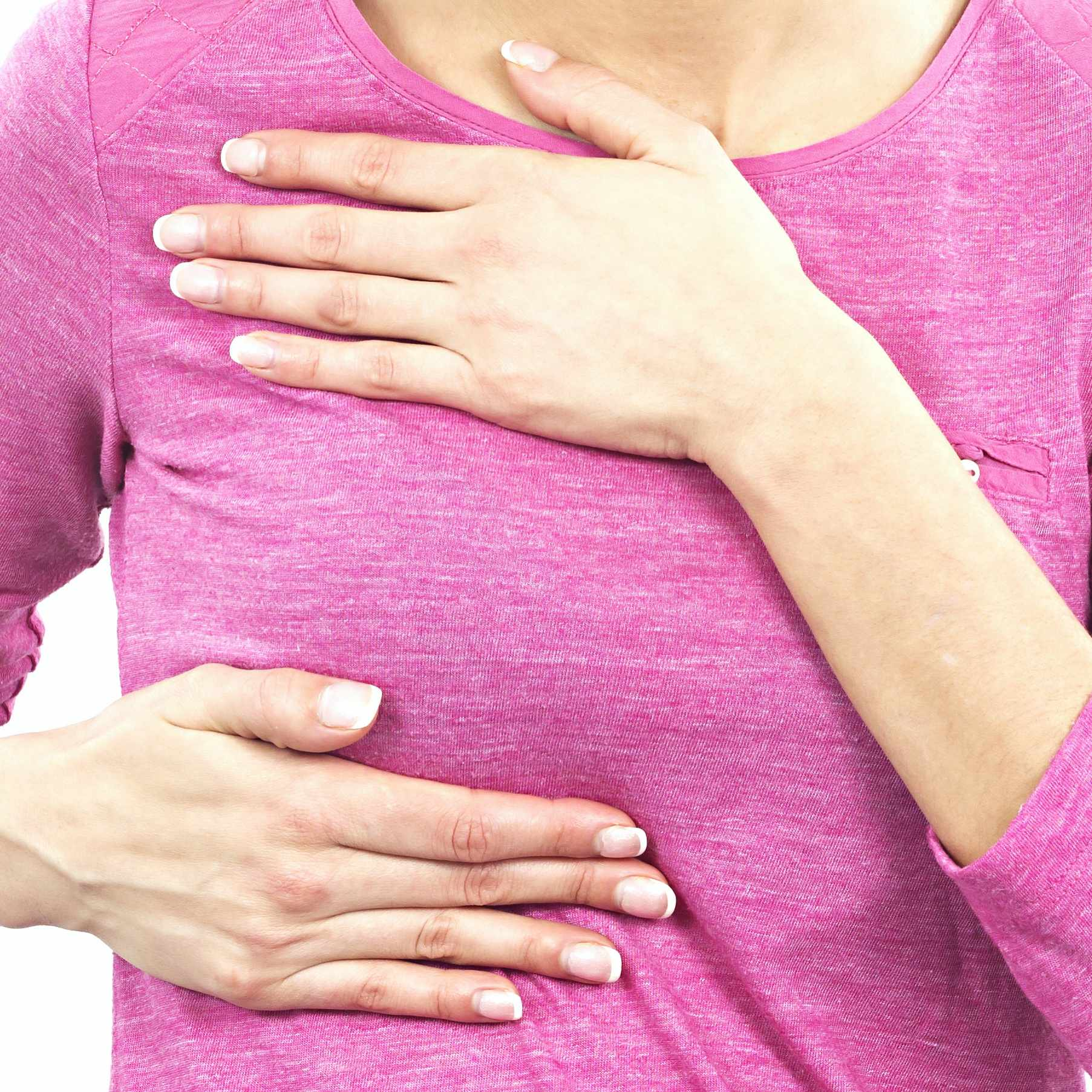 a woman in a pink shirt gently holding the top and bottom of her sore or tender breast