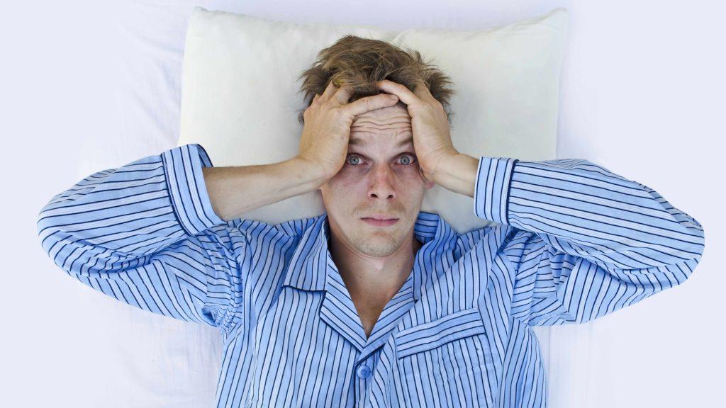 Un pobre hombre se despierta en la cama, pero no se siente descansado y se agarra la cabeza con las manos