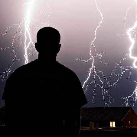 a man standing in a thunderstorm with lightning in the sky