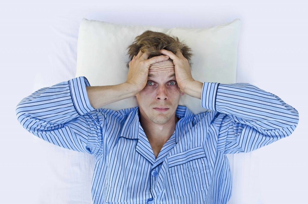 an unhappy man lying in bed, waking up but not well rested, with his hands clutching his head