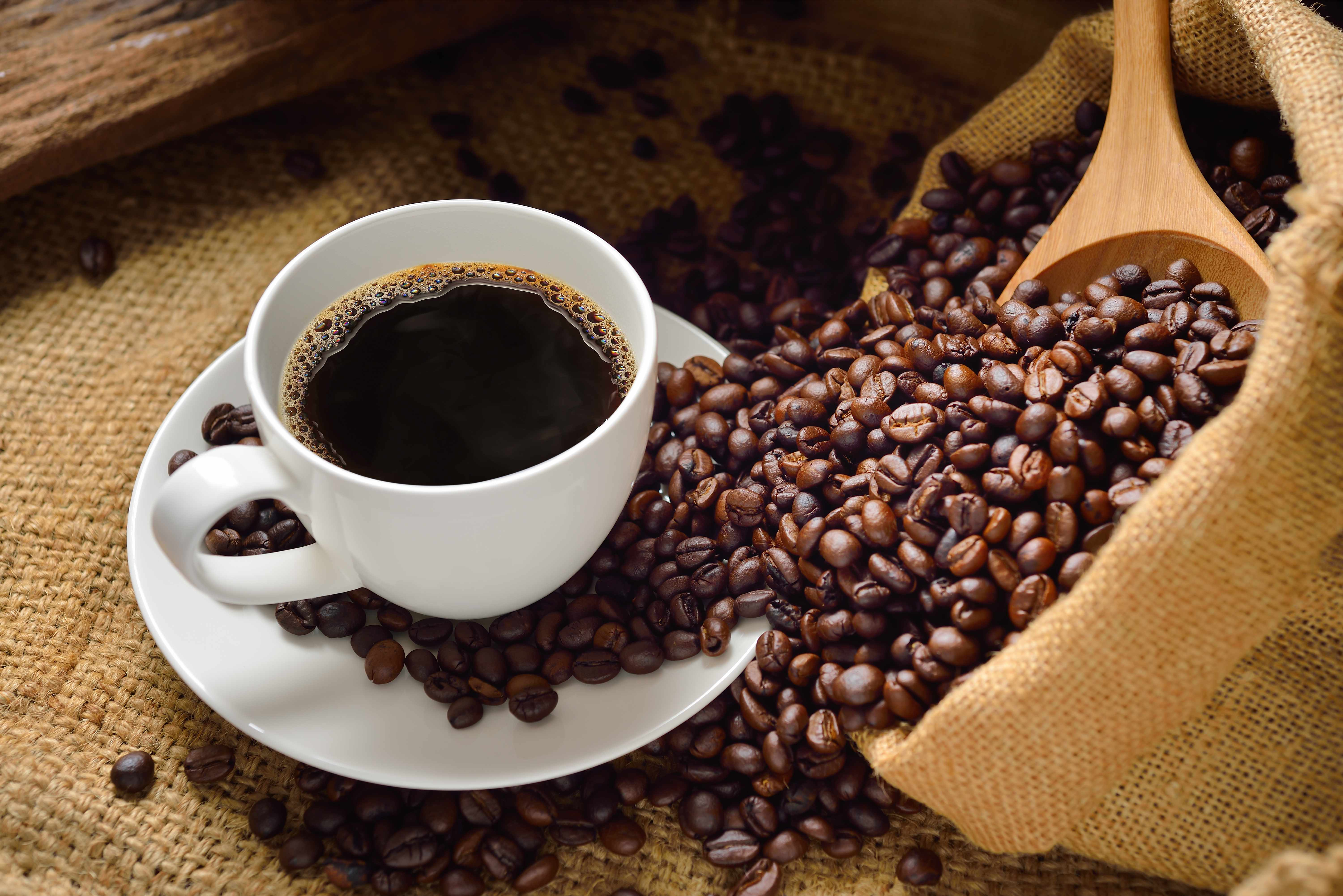 a cup of coffee on a burlap cloth and coffee beans spilling around the table