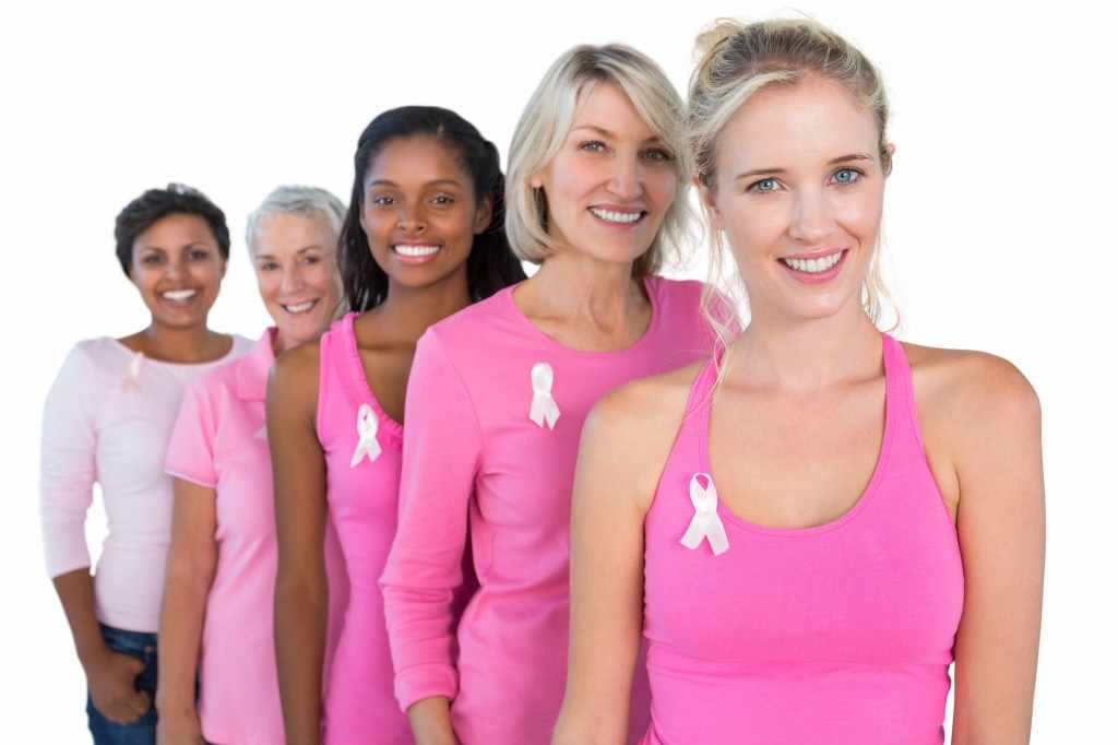a line of women wearing pink shirts representing breast cancer awareness