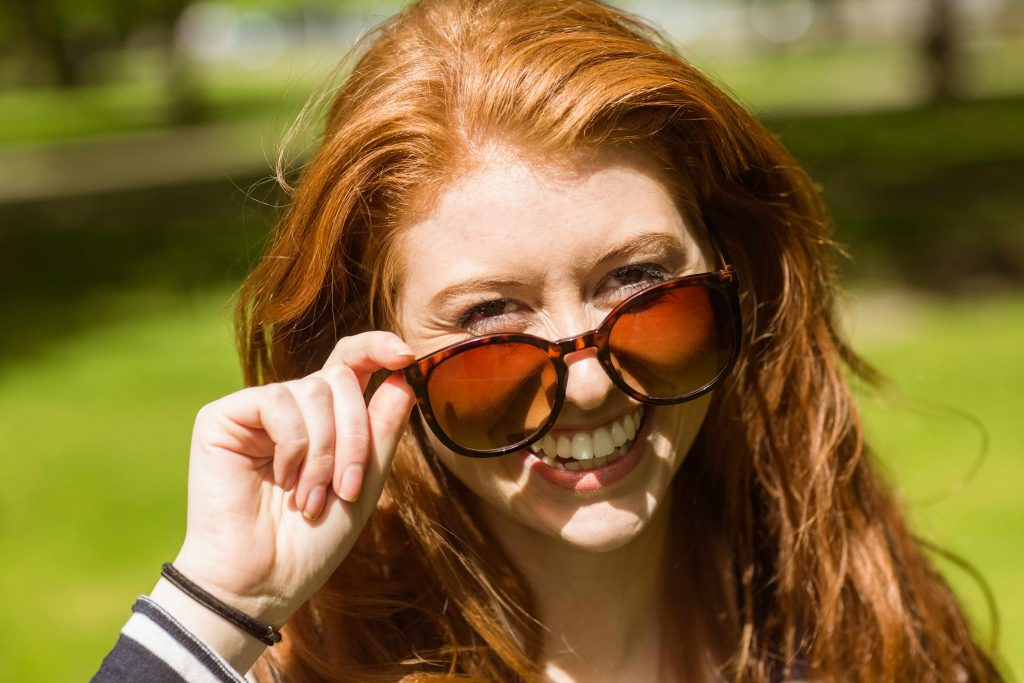 a smiling woman outside on a sunny day, peering over her sunglasses