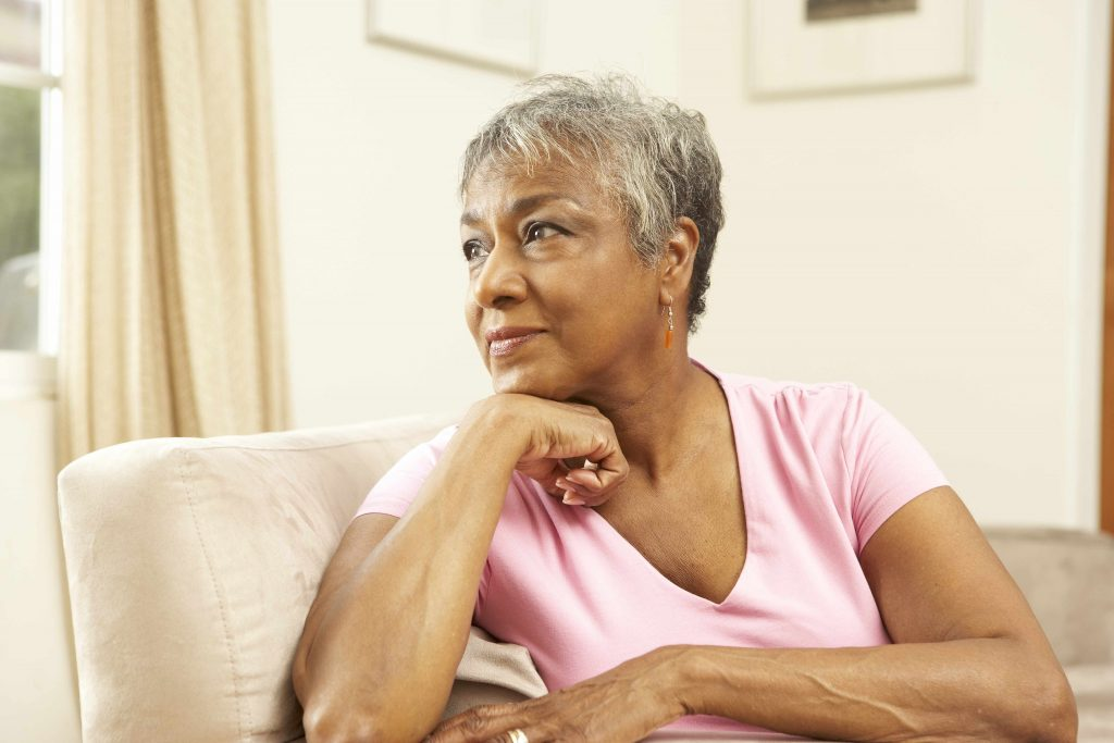 a middle-aged African American woman sitting in a chair and looking out a window